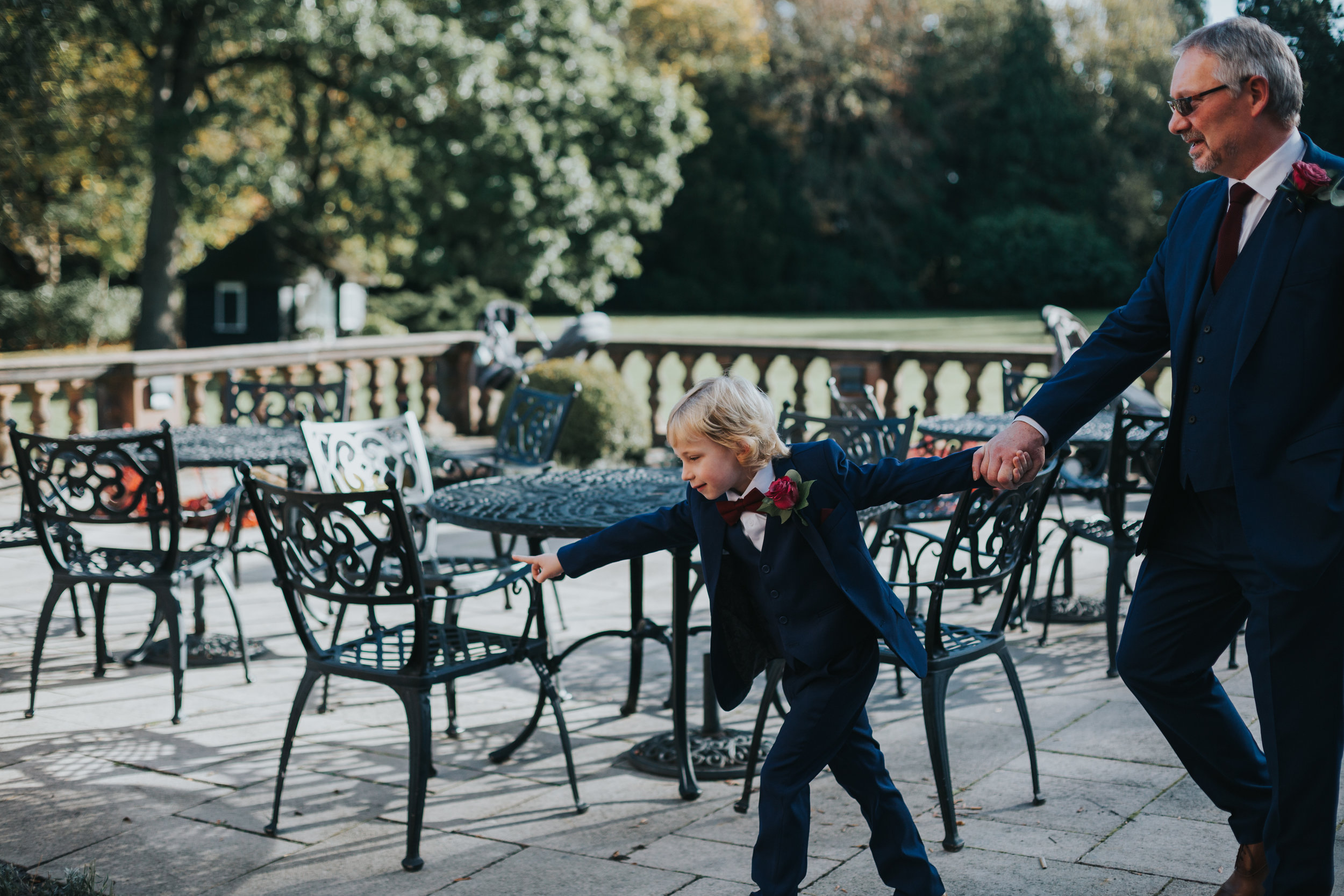 Small boy in a blue suit and red bow tie drags an older groomsmen across the patio.