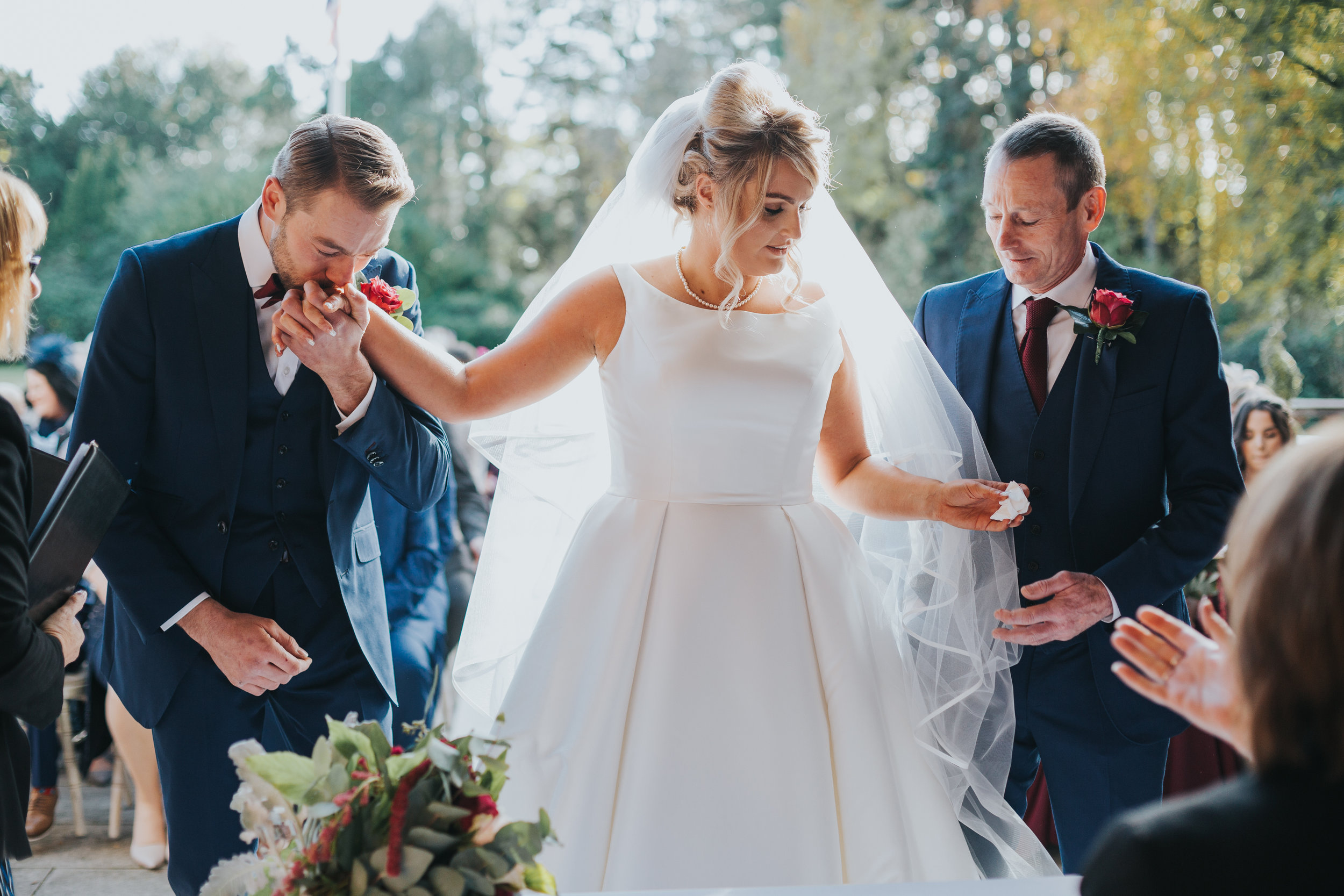 The Groom kisses the brides hand, while her father gives her a tissue to wipe their tears and snot probably.