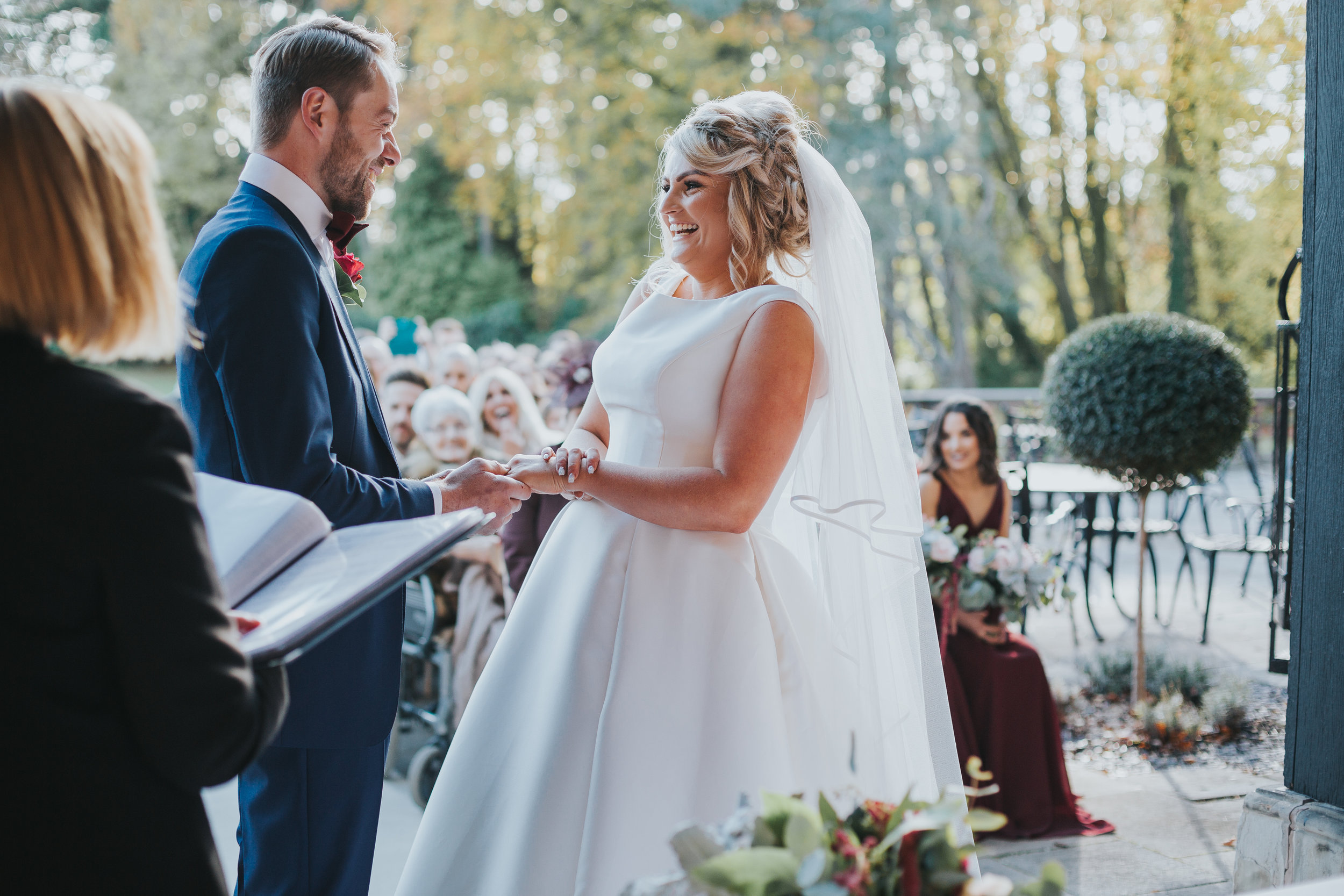 Bride and Groom hold hands laughing as they say their vows during outdoor ceremony.