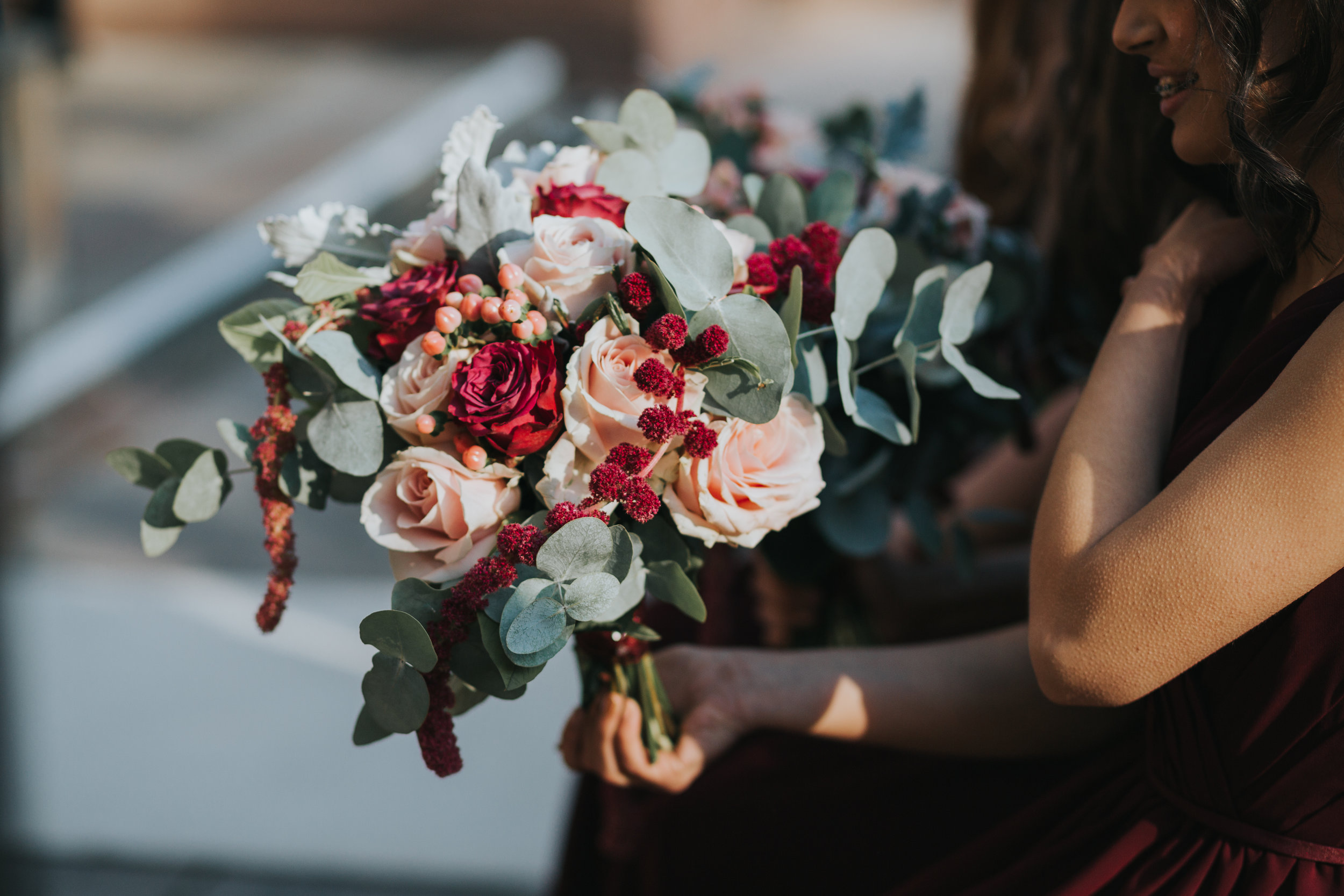 Close up of bouquet of flowers including red roses and berries, pink roses and eucalyptus branches.