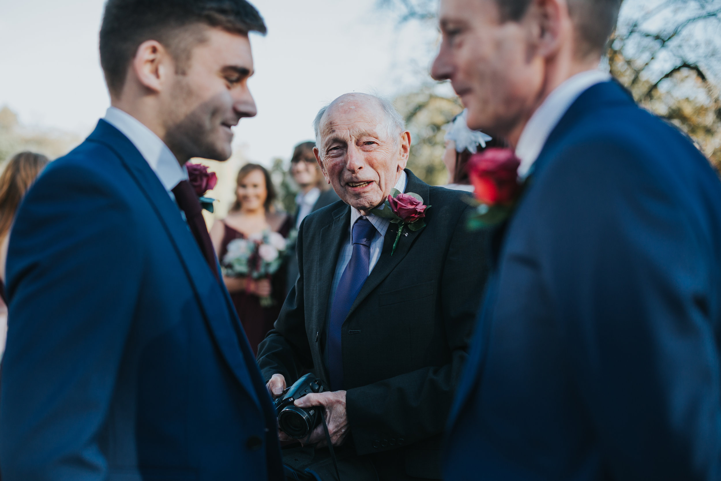 Older male wedding guest holds his camera, framed by two male wedding guests wearing blue.