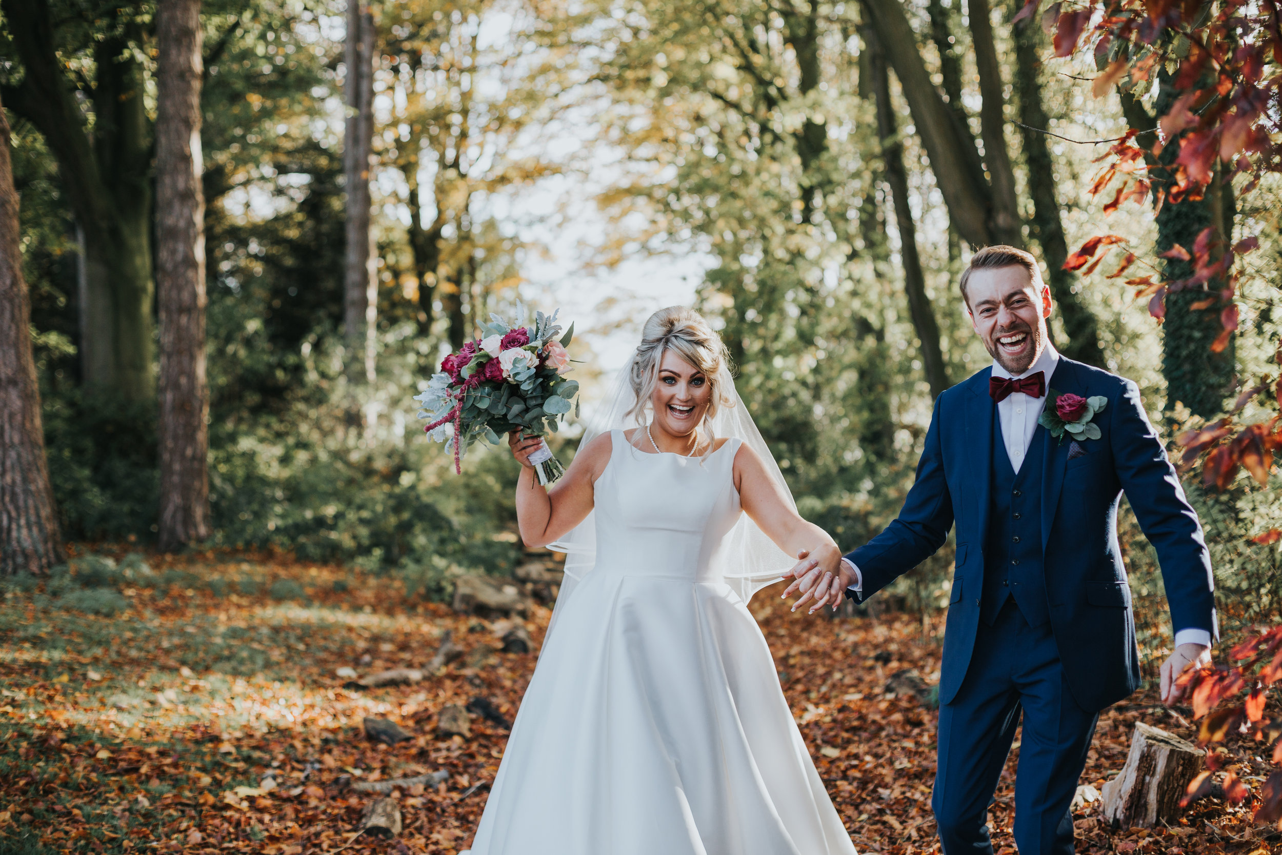 Husband and wife walk through the tree lined path together laughing after their Autumnal wedding ceremony at Inglewood Manor.