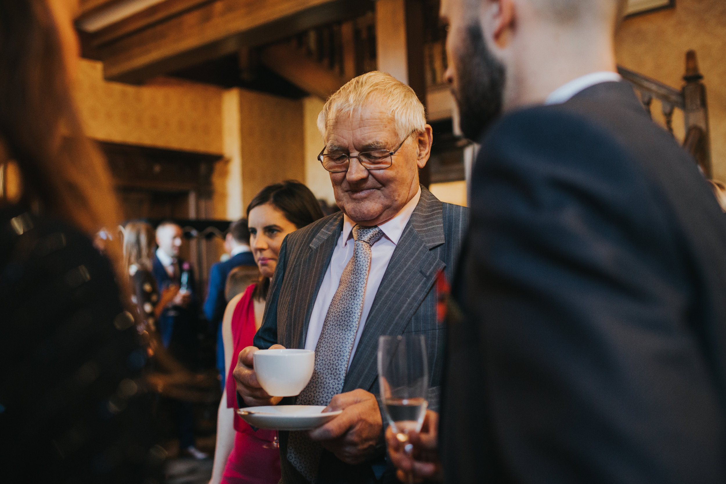 Older male wedding guest enjoys a cup of tea at a wedding reception at Inglewood Manor