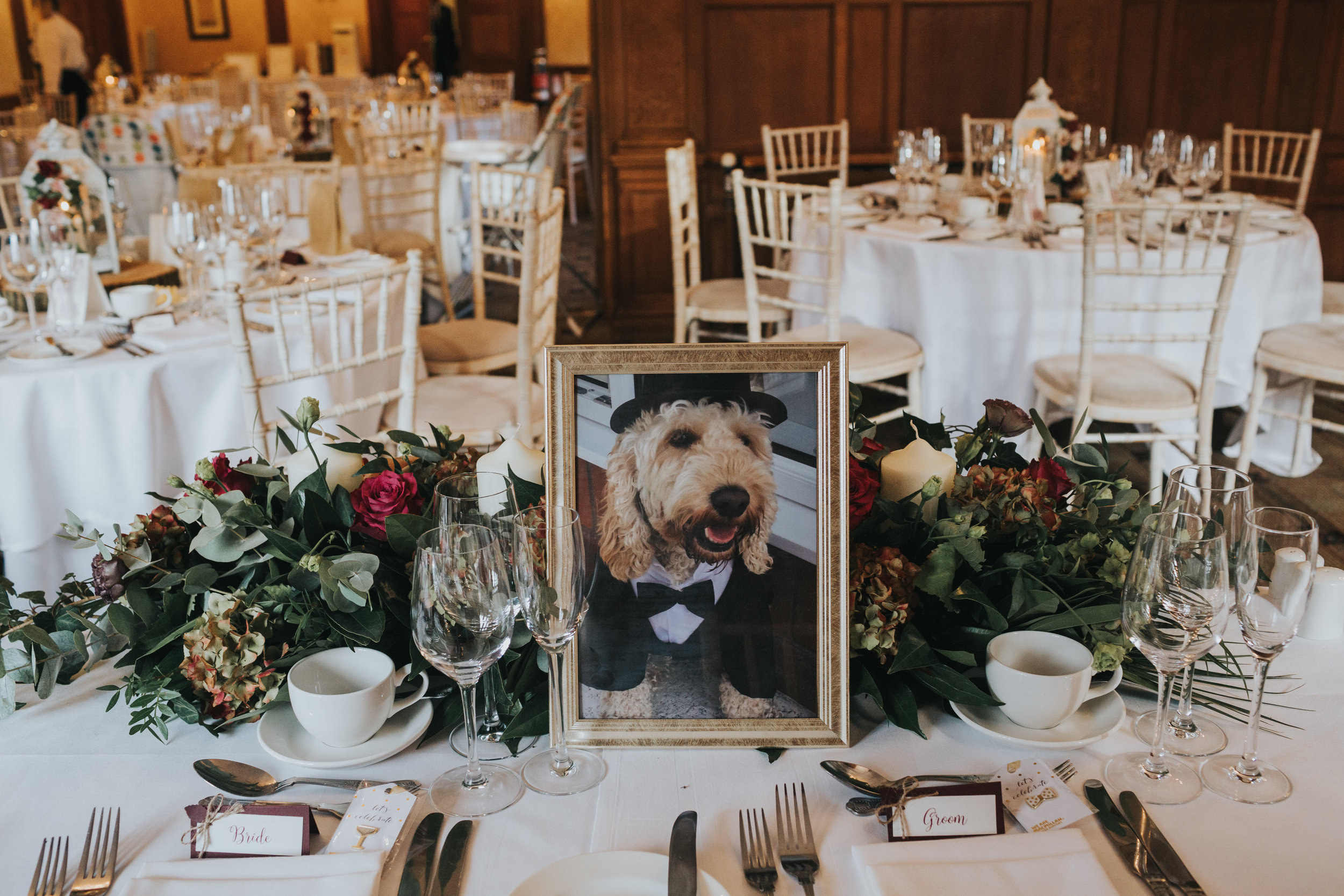 A photograph of the bride and grooms dog awaits them at their table.