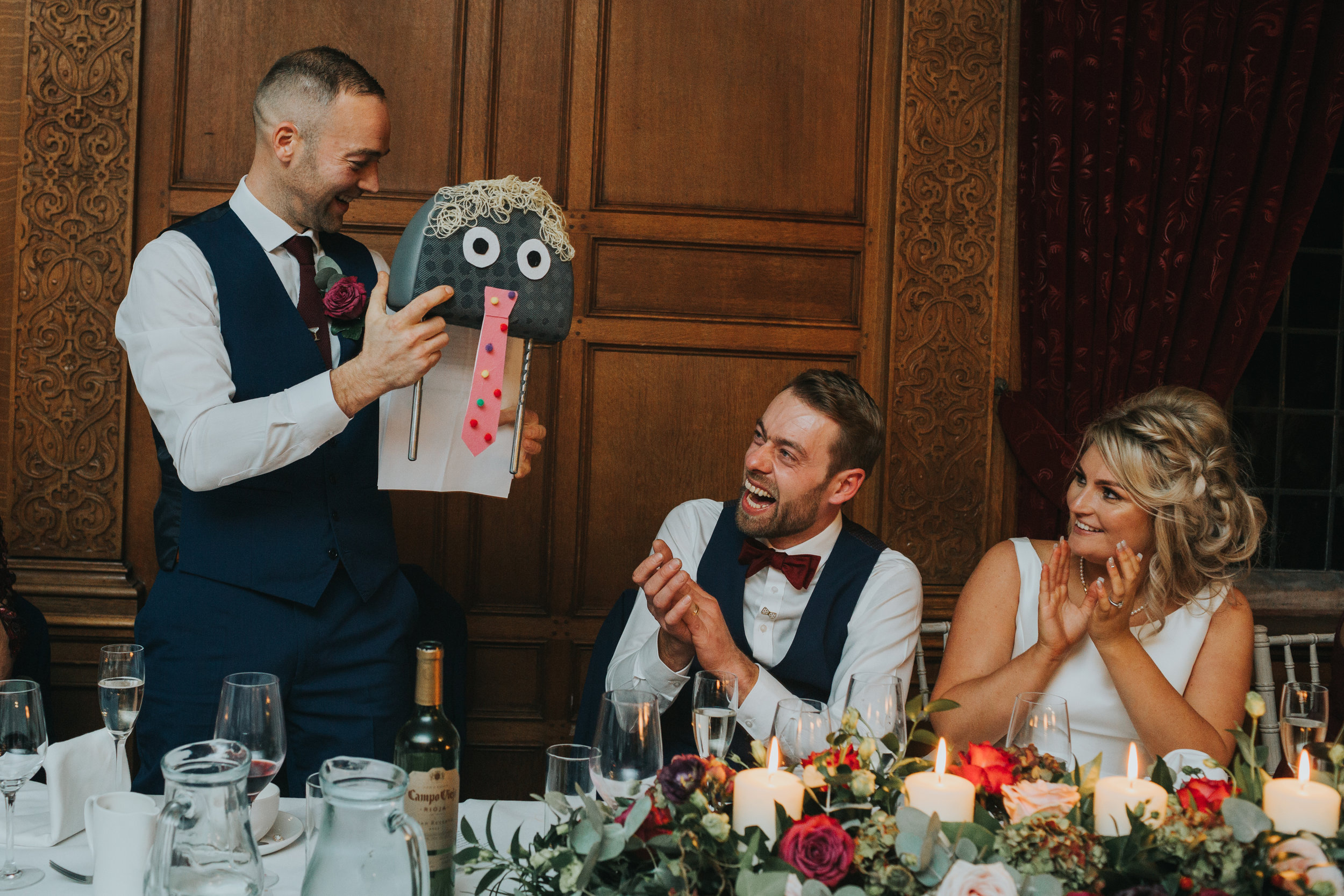 The best man presents the Groom with a car seat made up to look like a person.