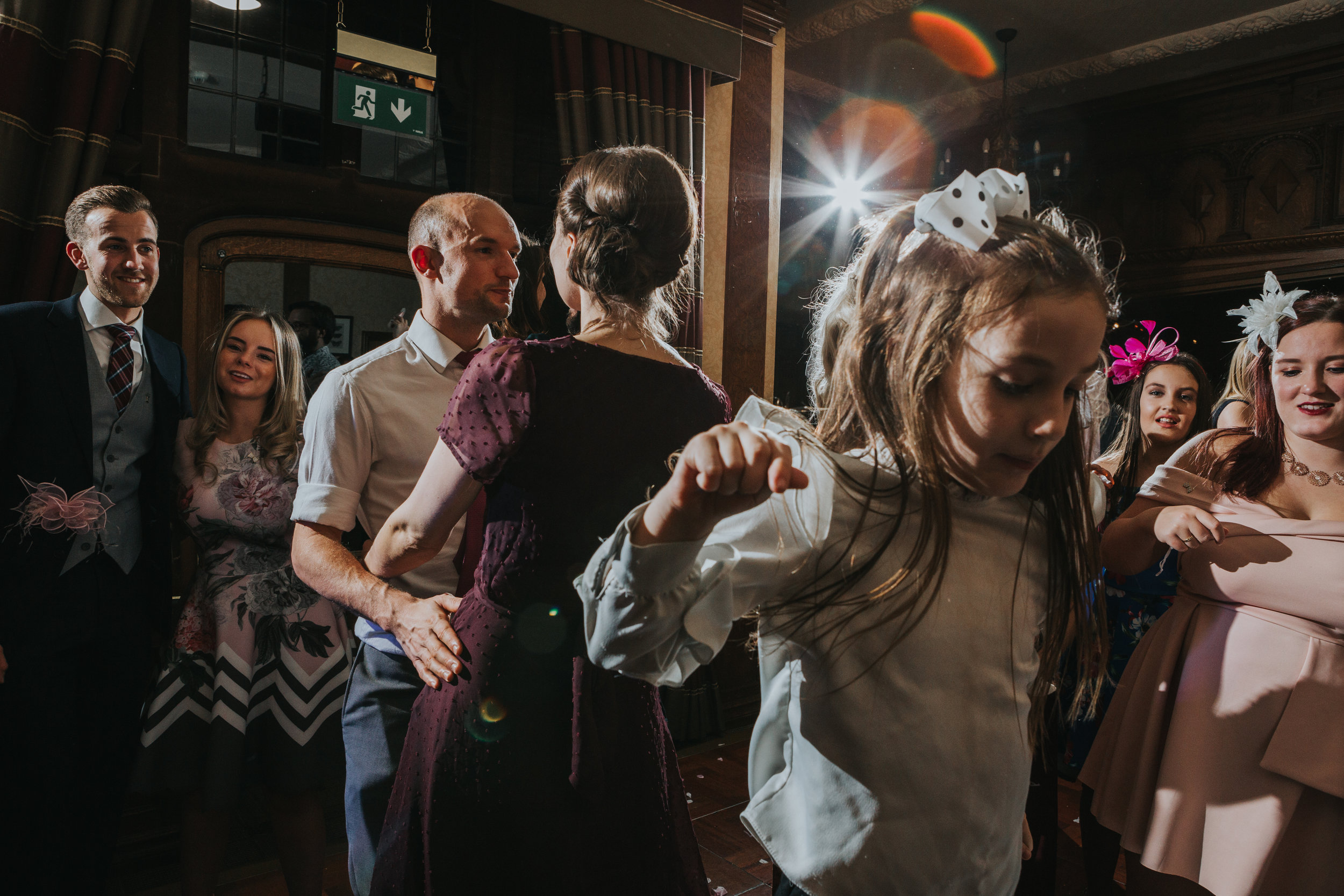 Wedding guests hit the dance floor, a little girl jumps up and down as wedding guests dance behind her.