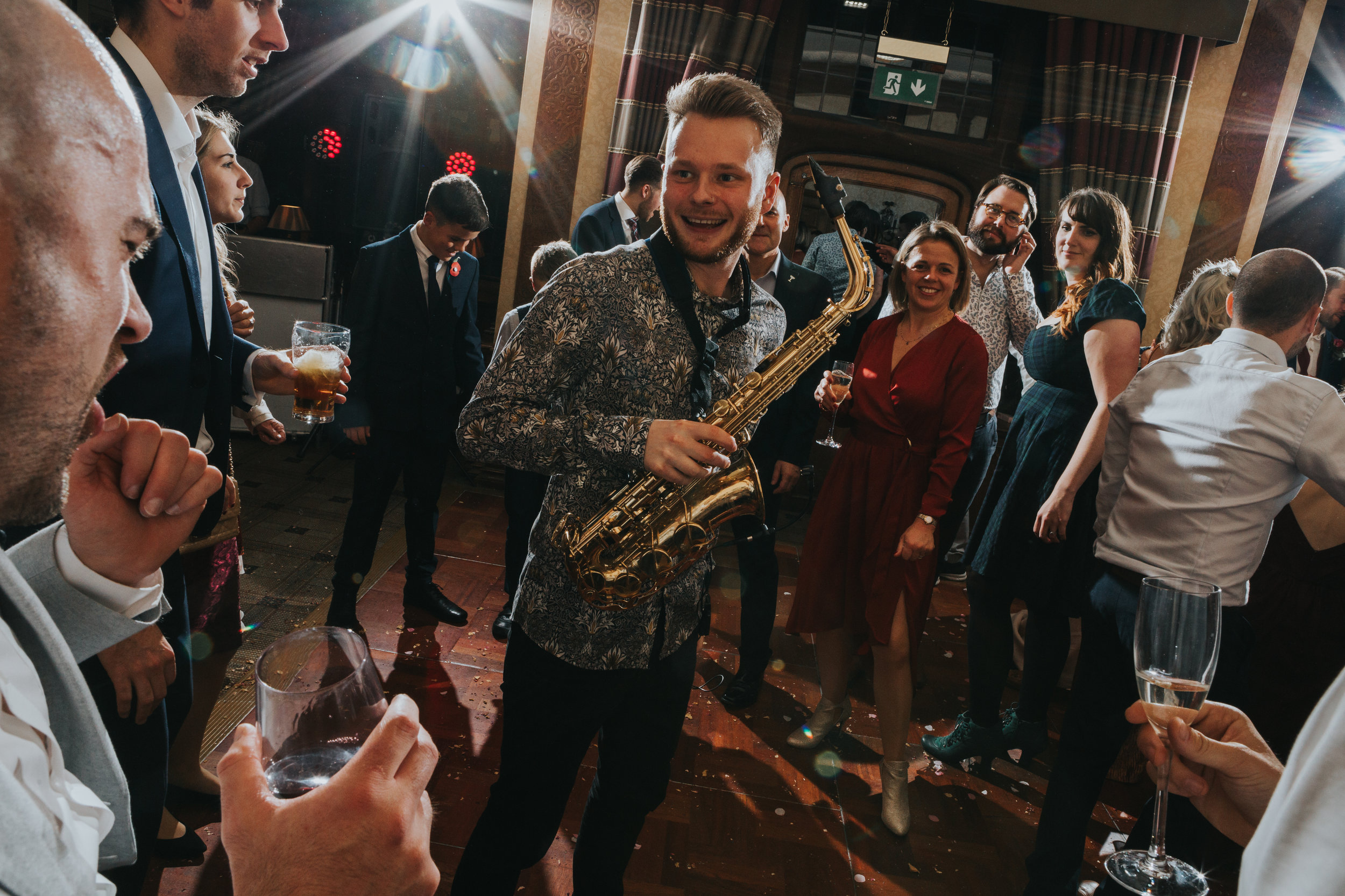 Saxophone player smiles at guests giving it their all on the dance floor.