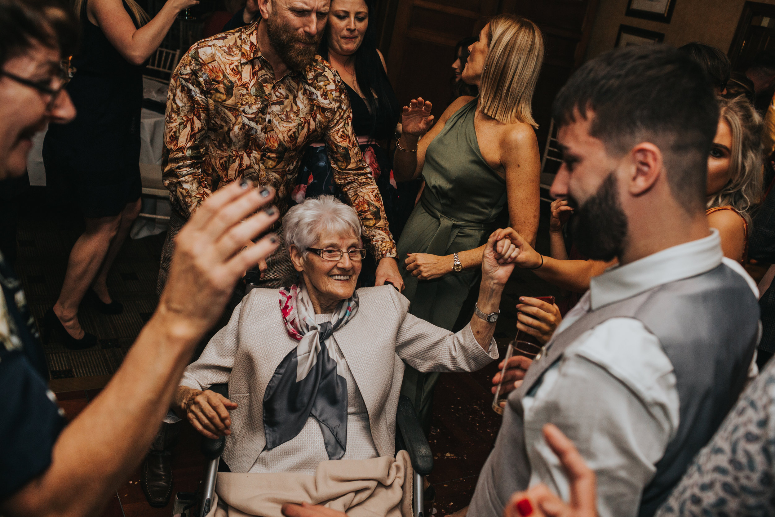 Grandma dances in her wheelchair surrounded by friends and family.