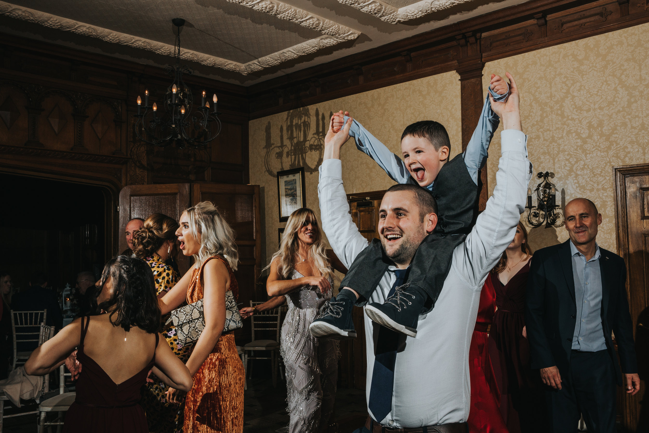 Little boy sits on his dads shoulders cheering as wedding guests dance around them.
