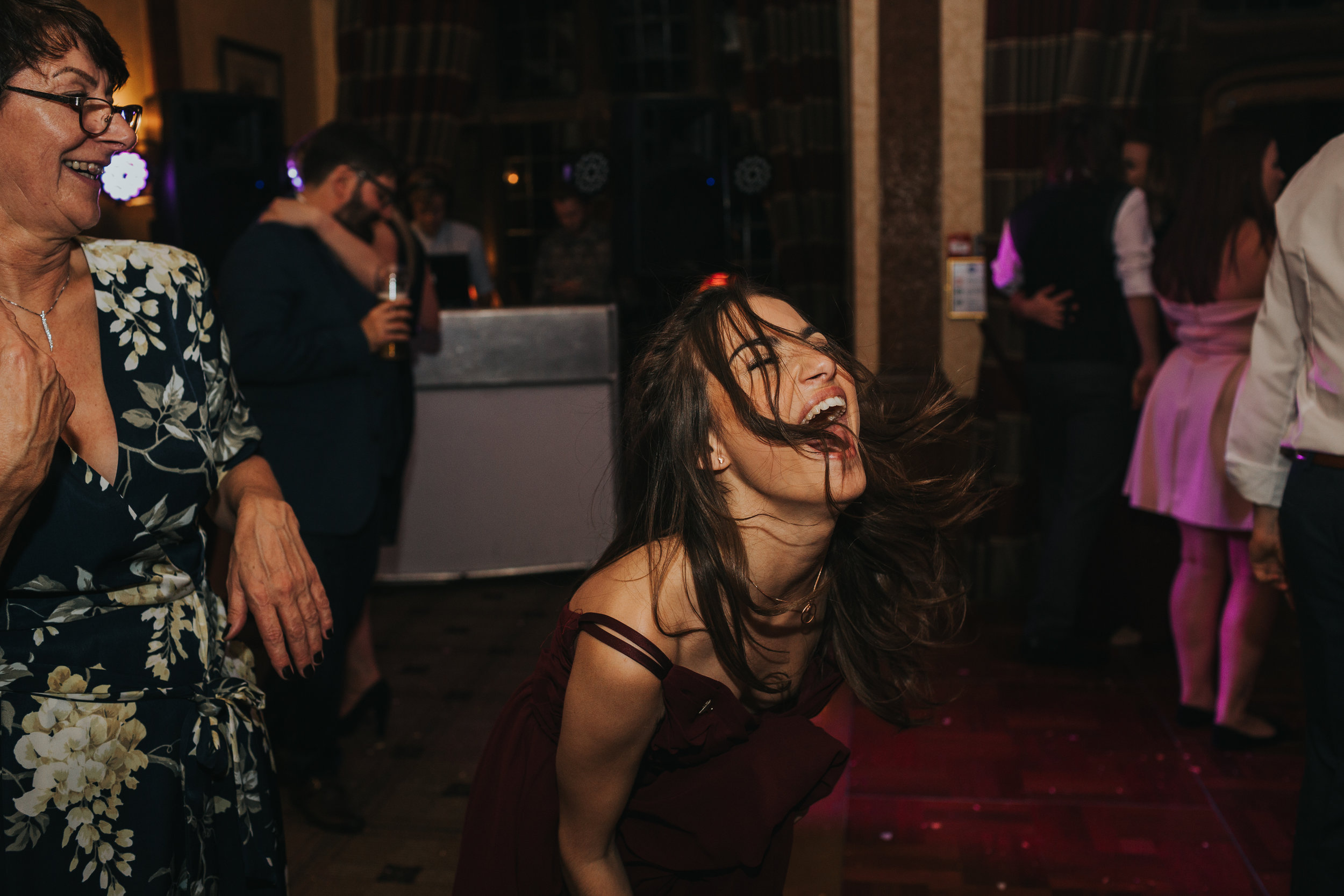 Bridesmaid shouts out and throws her head back as she dances.