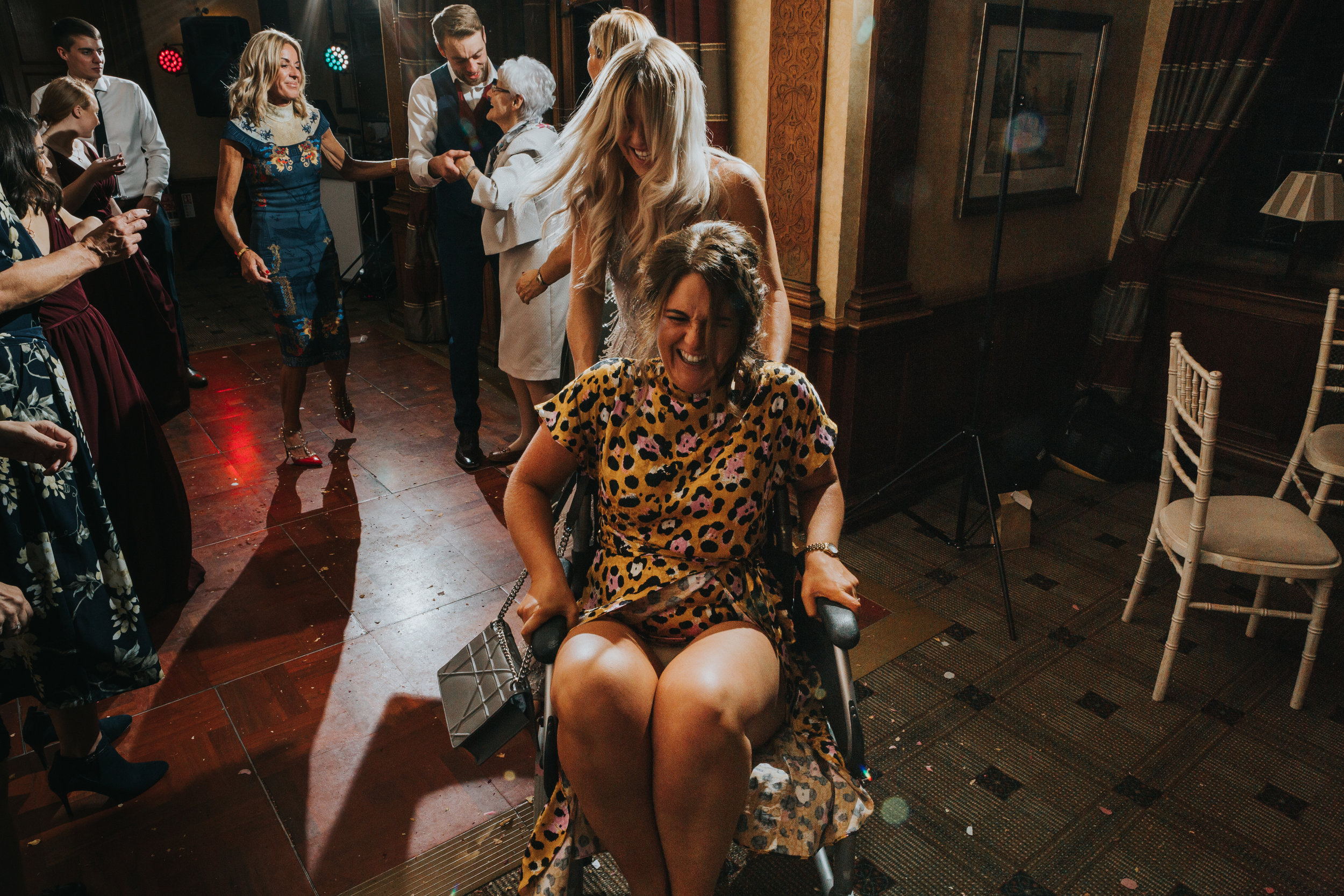 Wedding guest laughs as she is driven around in Grandma's wheelchair.