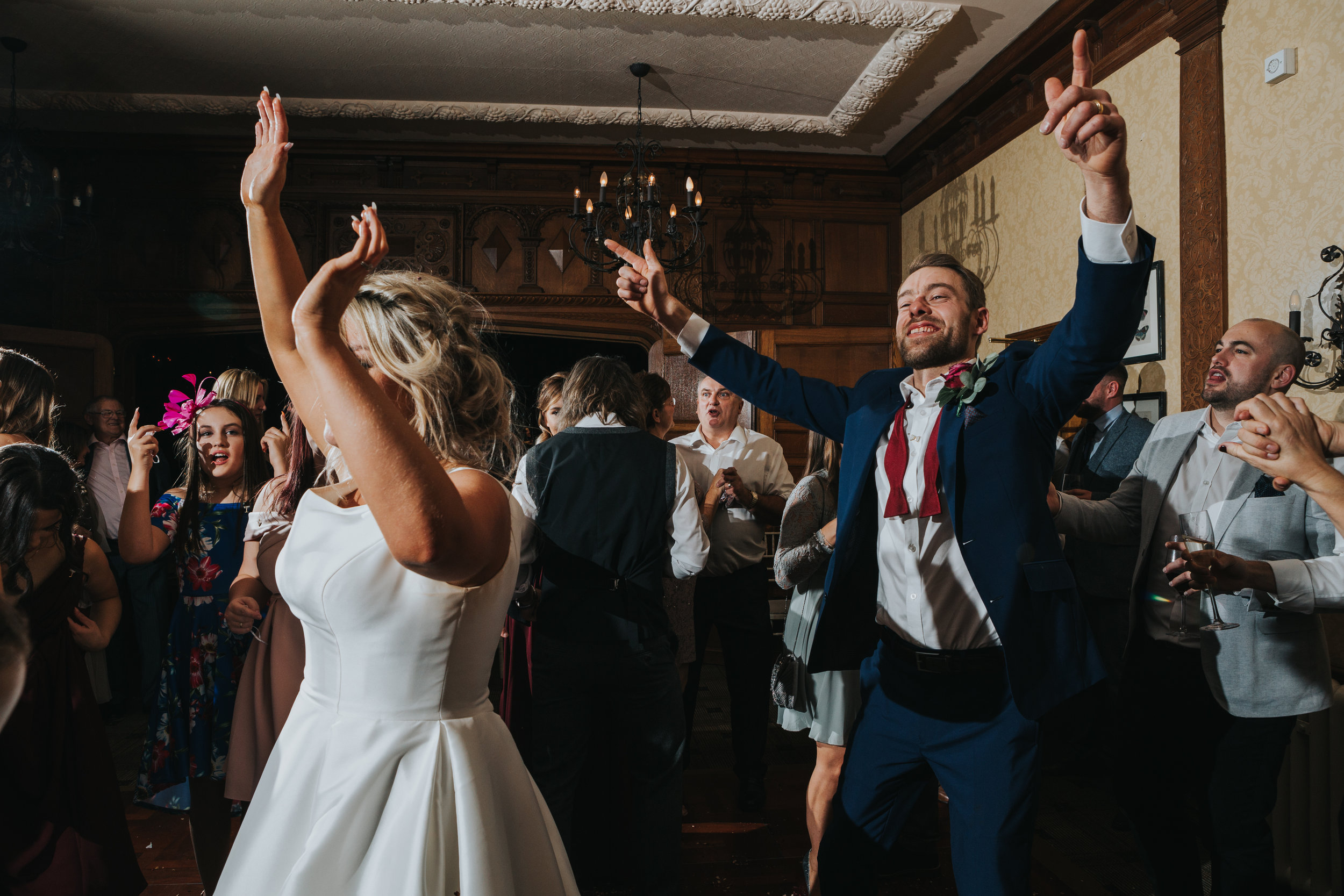Groom stands nest to his new wife holding both hands in the air while grinning from ear to ear, surrounded by his friends and family.