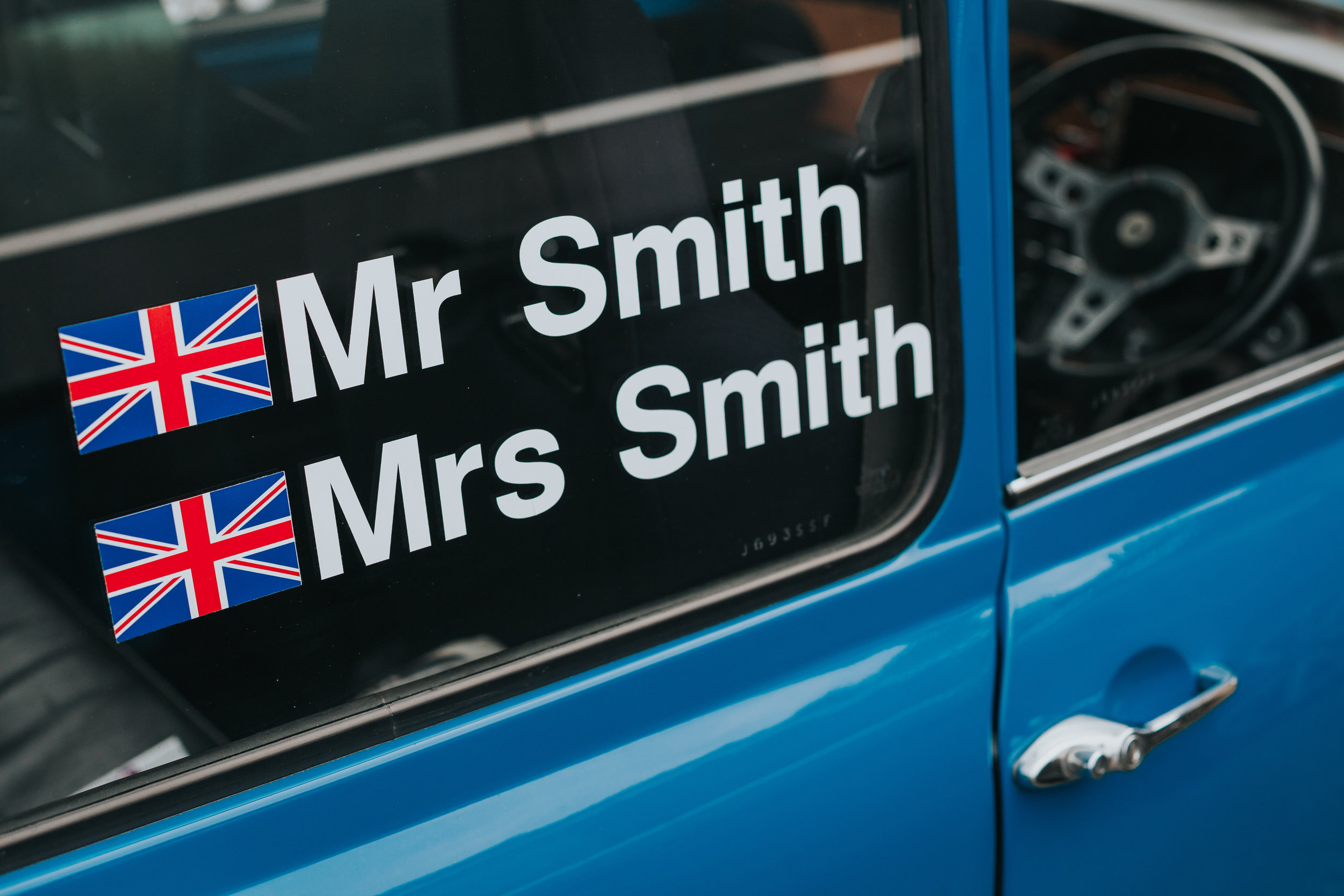 Window of a blue mini, with Mr and Mrs Smith written on it.