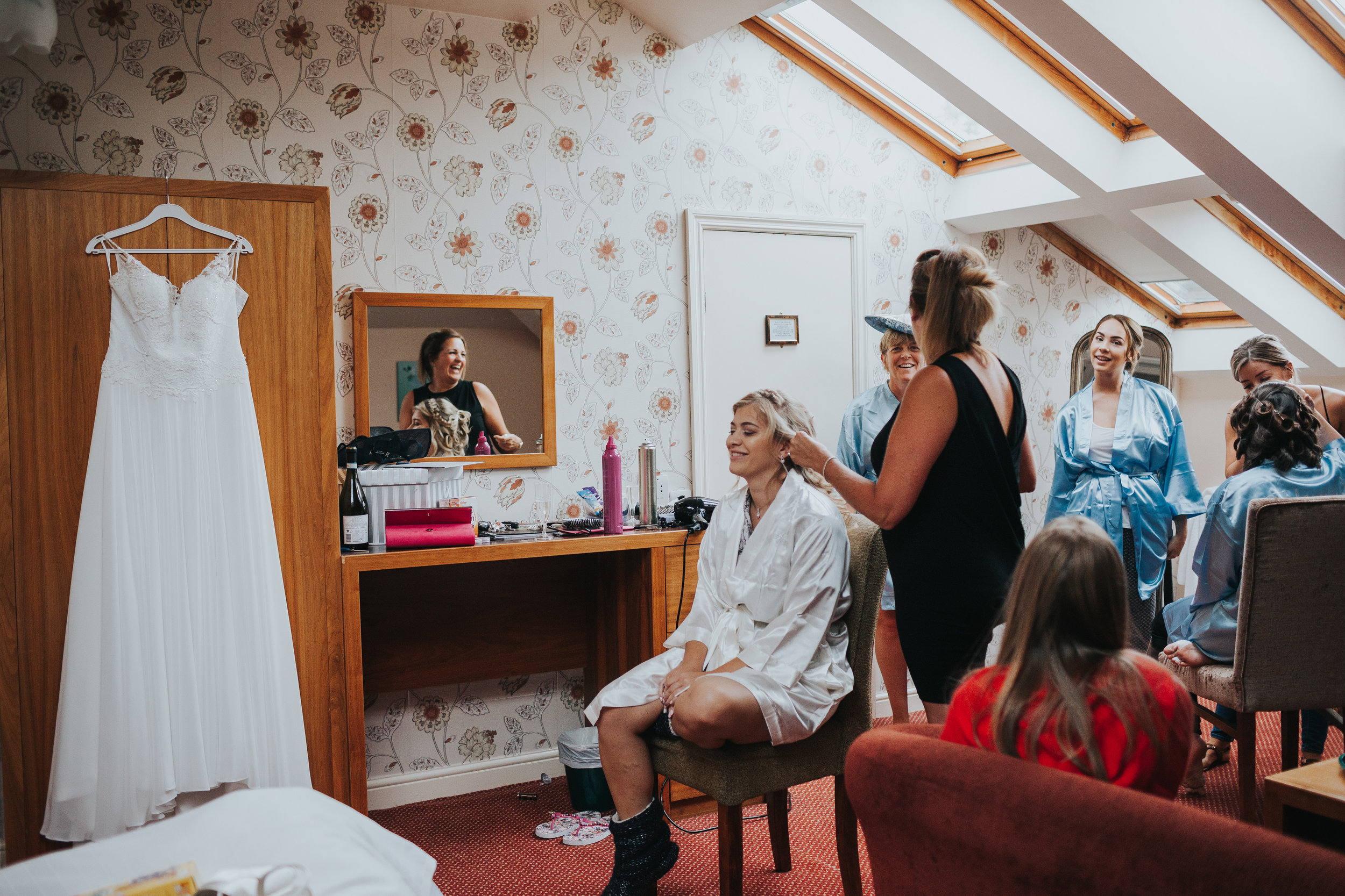 Bride gets her hair done while looking at her wedding dress.