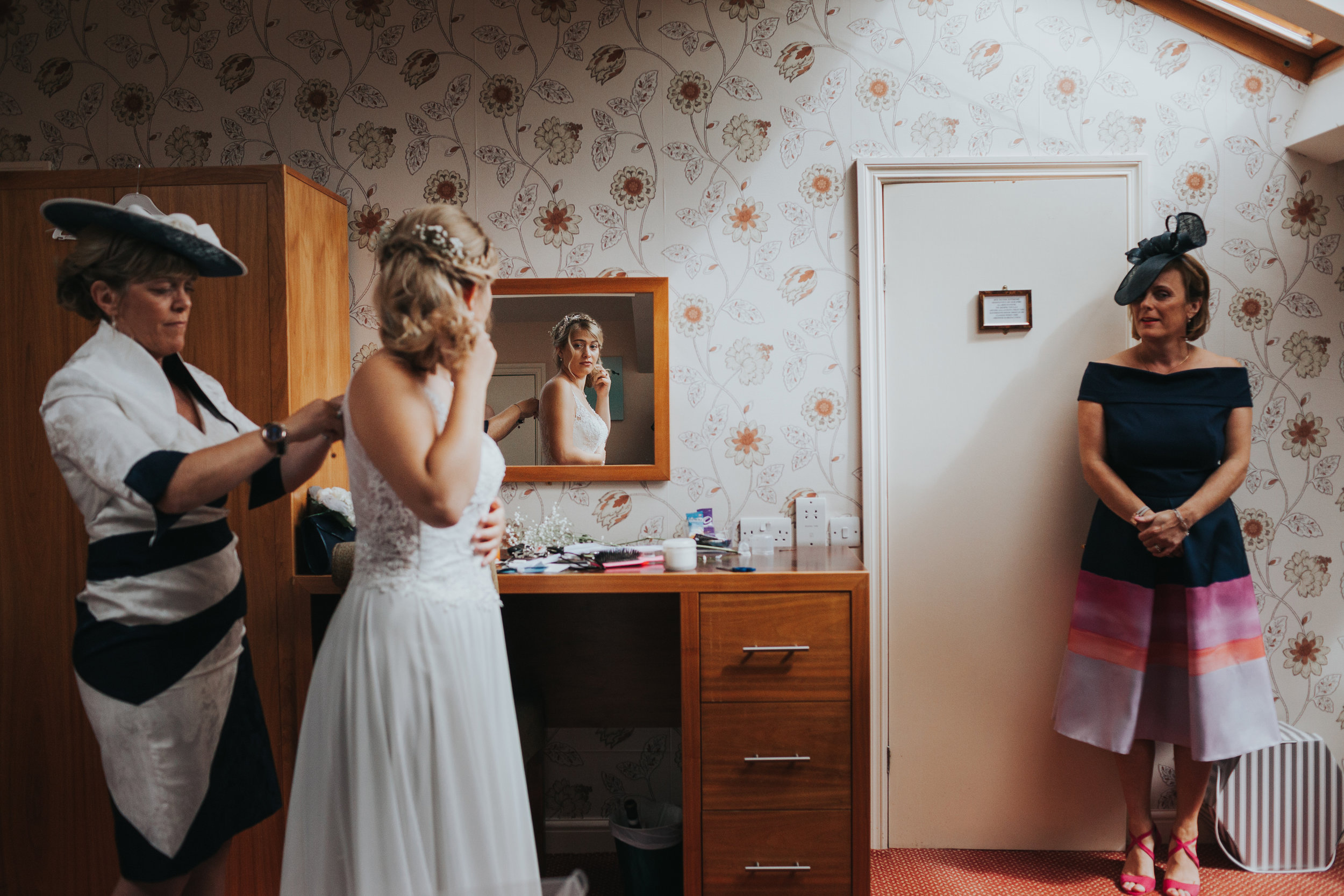 The bride to be is helped into her dress by her mother at Mytton Folds.