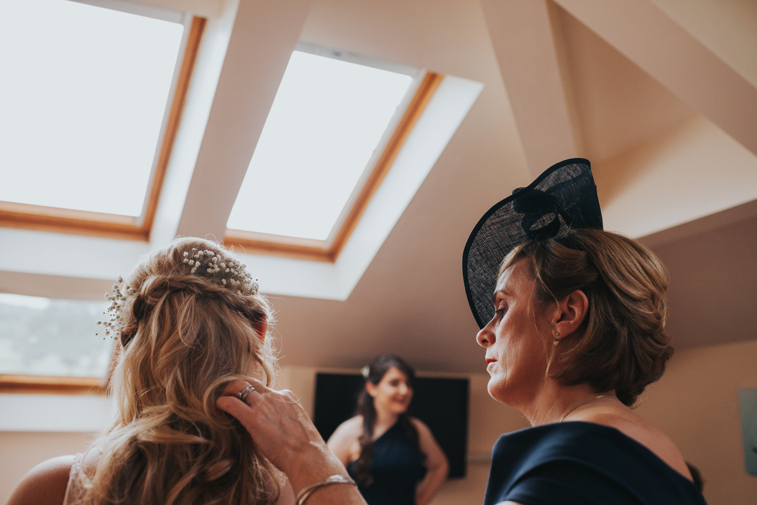Mother of the bride fixes her daughters hair.