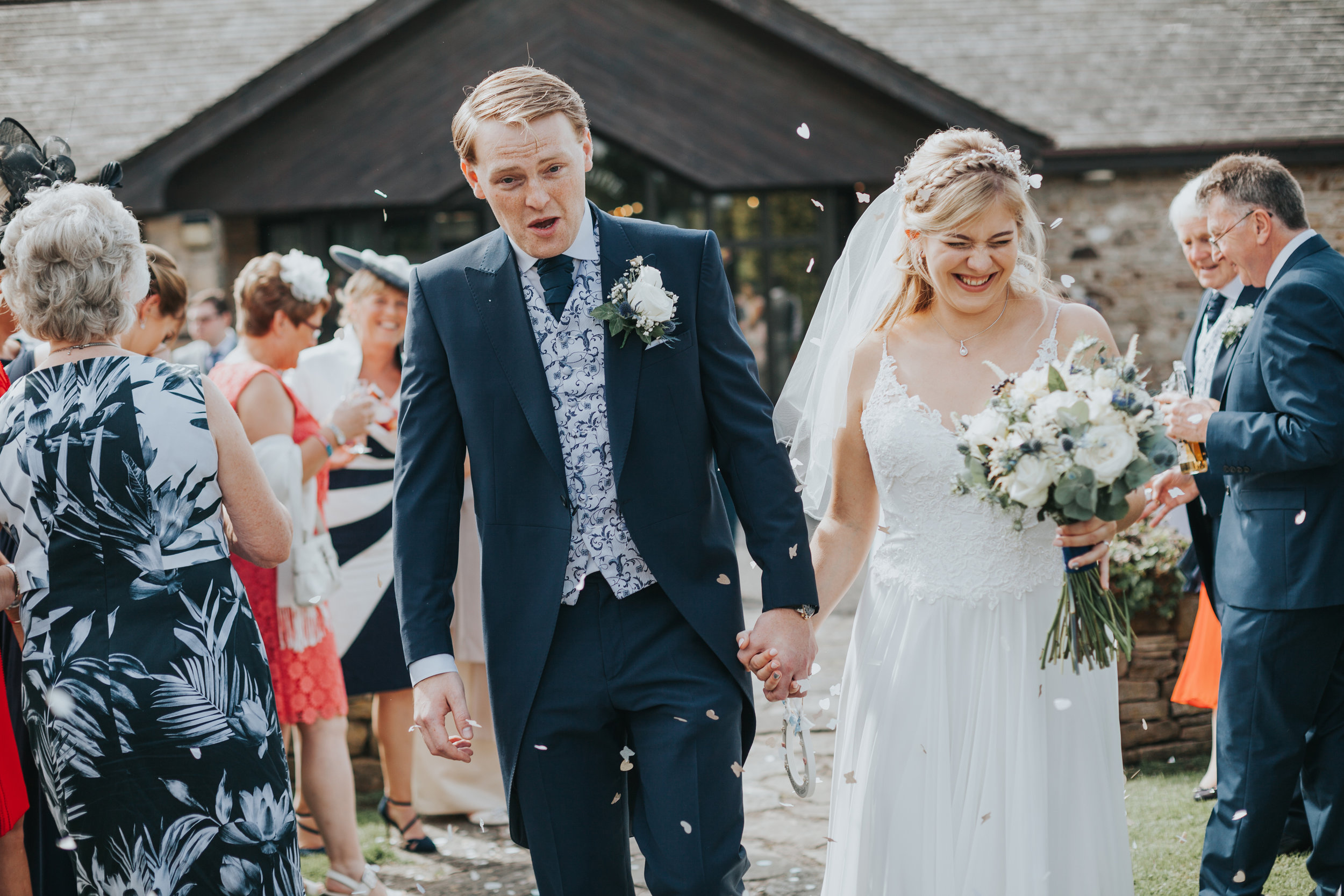 Bride and groom have confetti thrown at them outside the ceremony room at Mytton Fold.