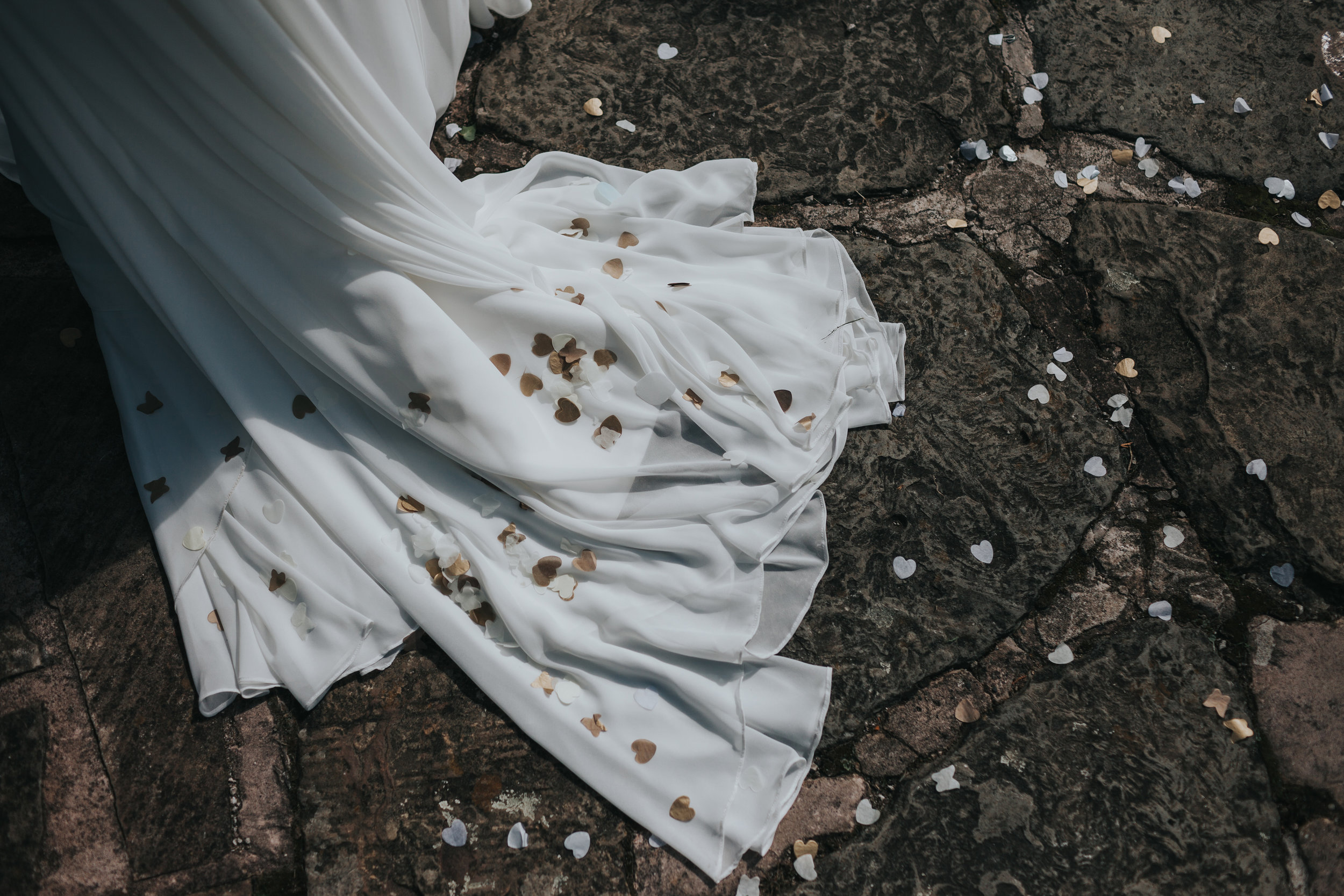 The trail of the Brides wedding dress is covered in heart shaped confetti.