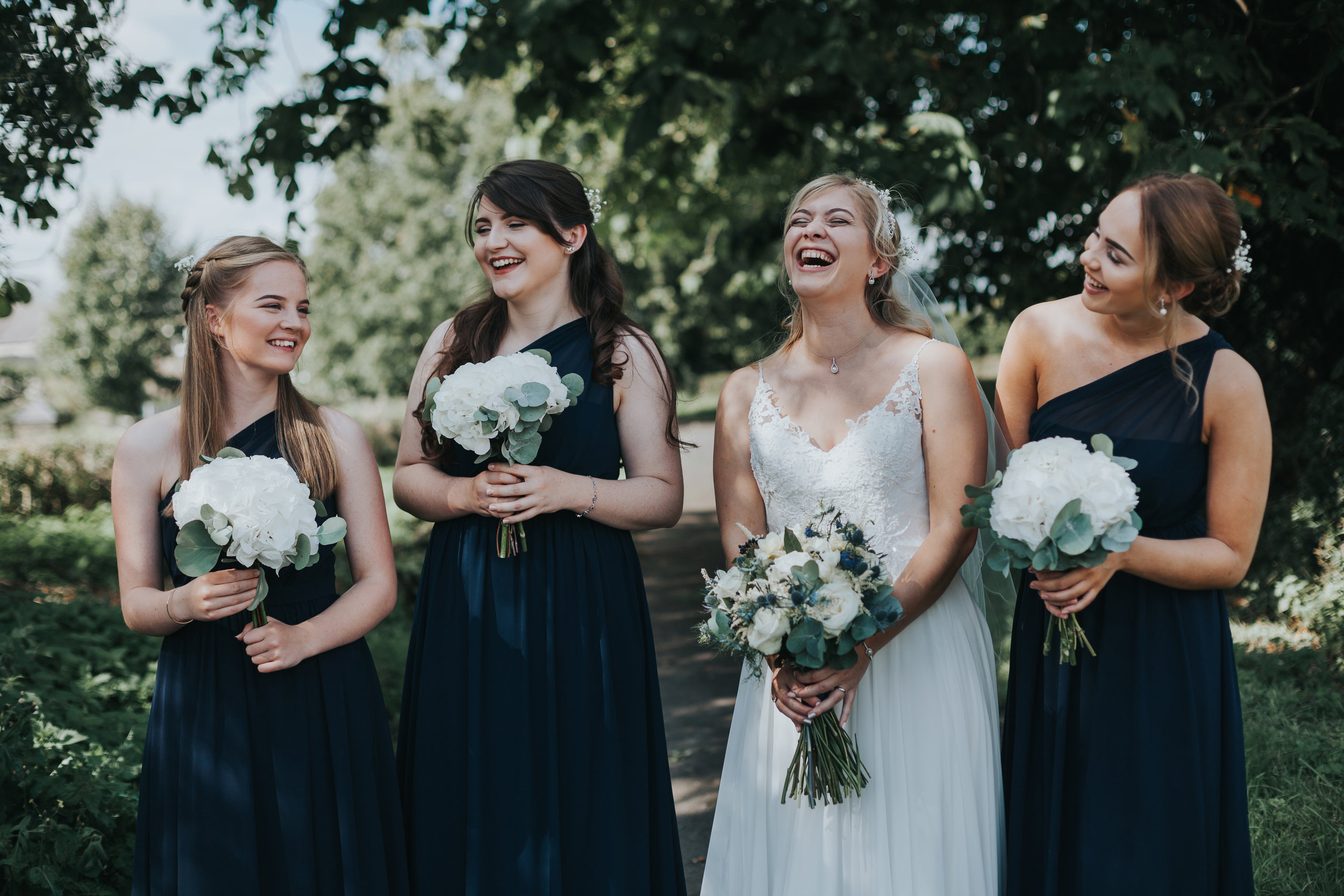 Bride laughs with bridesmaids.