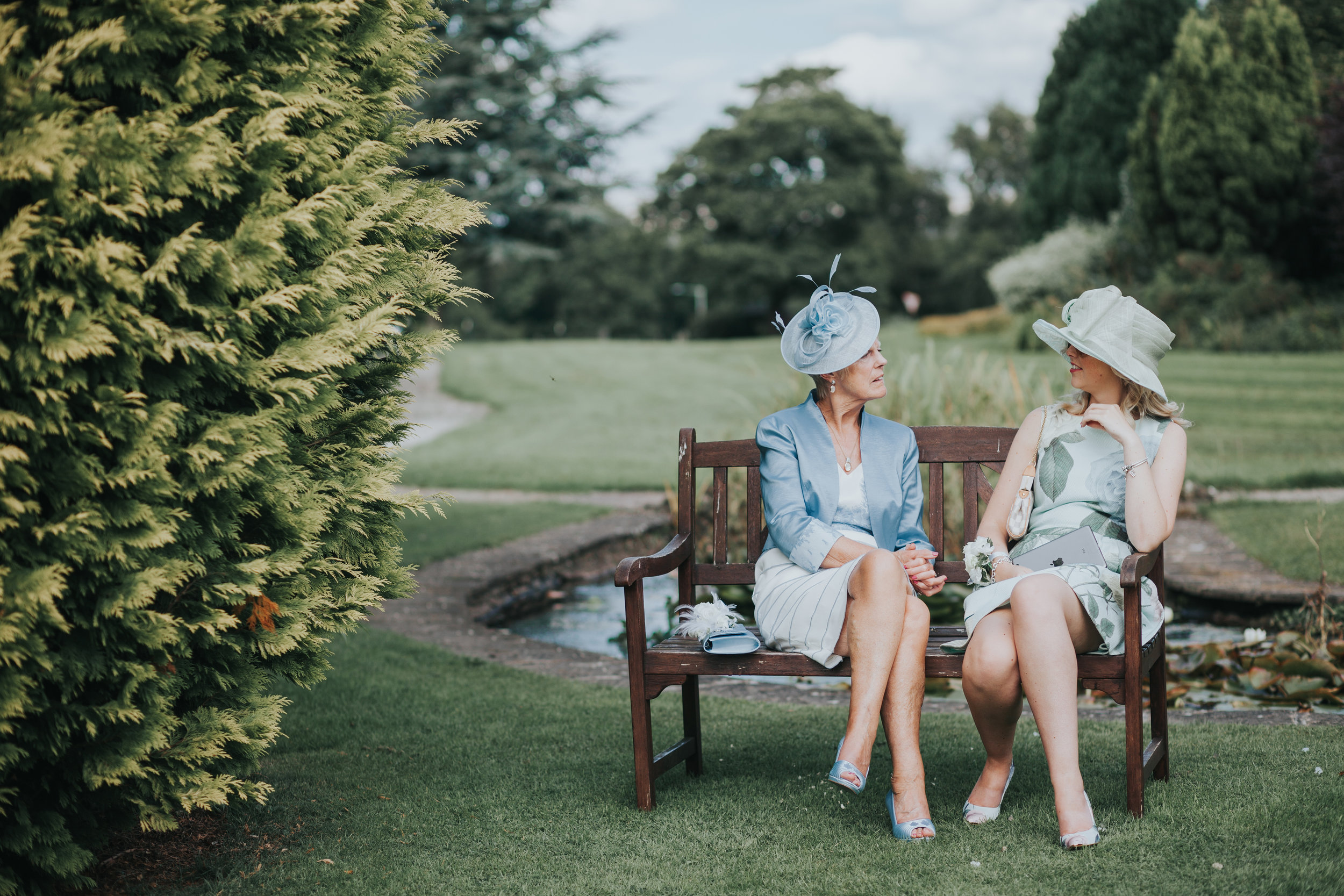 Wedding guests wearing pale green and blue outfits and hats sit together on the bench at Mytton Fold.