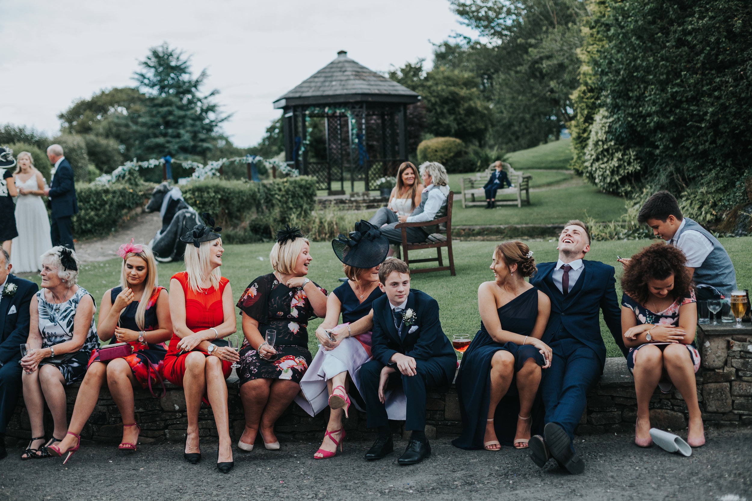 Wedding guests sit on a wall together laughing and drinking.