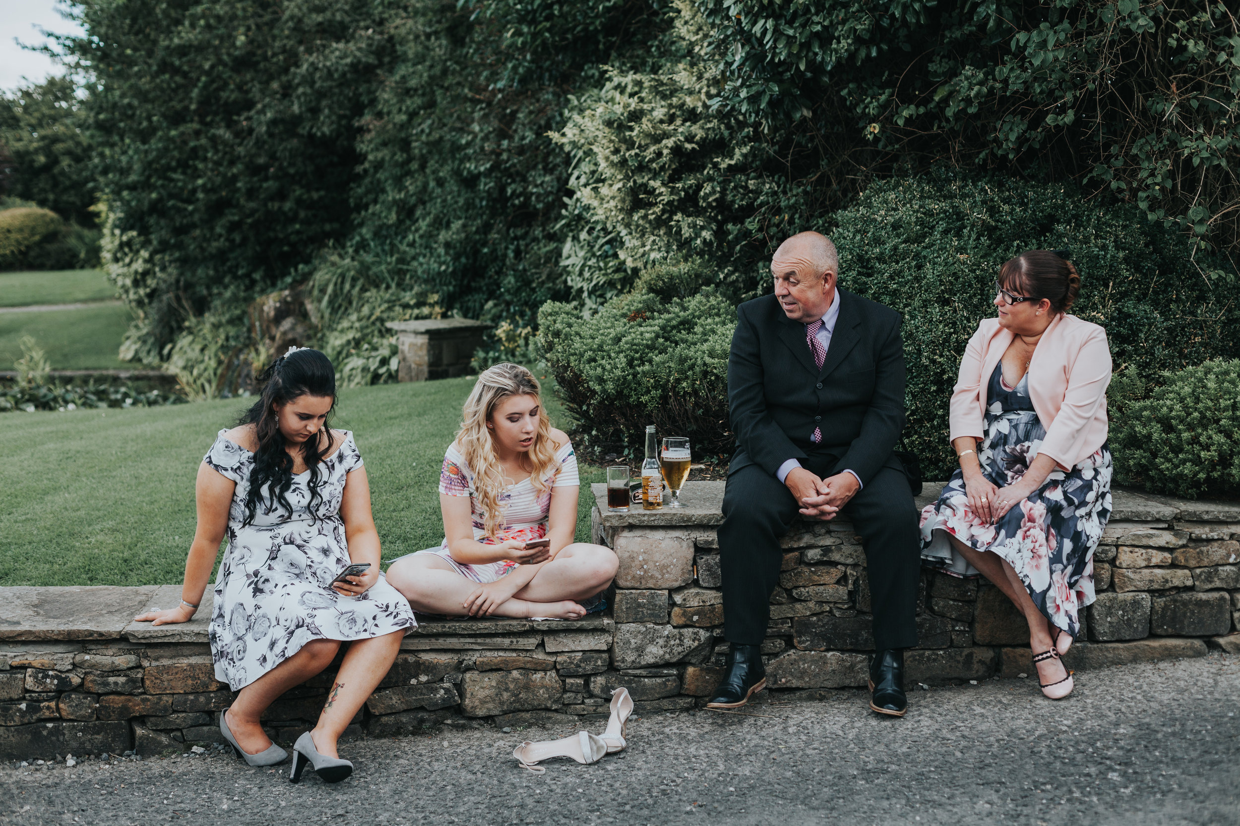 Four wedding guests sit together, one has given up on her shoes already.