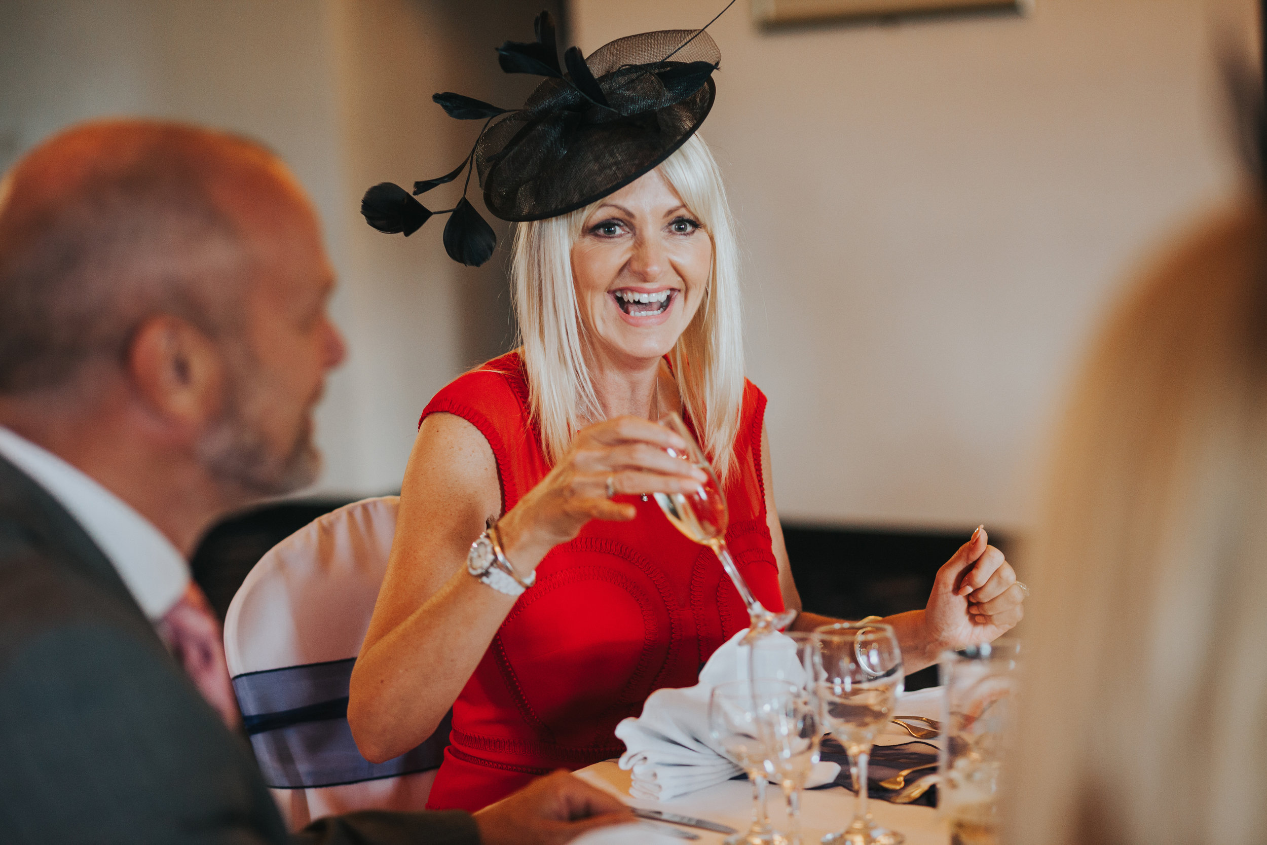 Wedding guest wears a red dress and black hat while laughing.