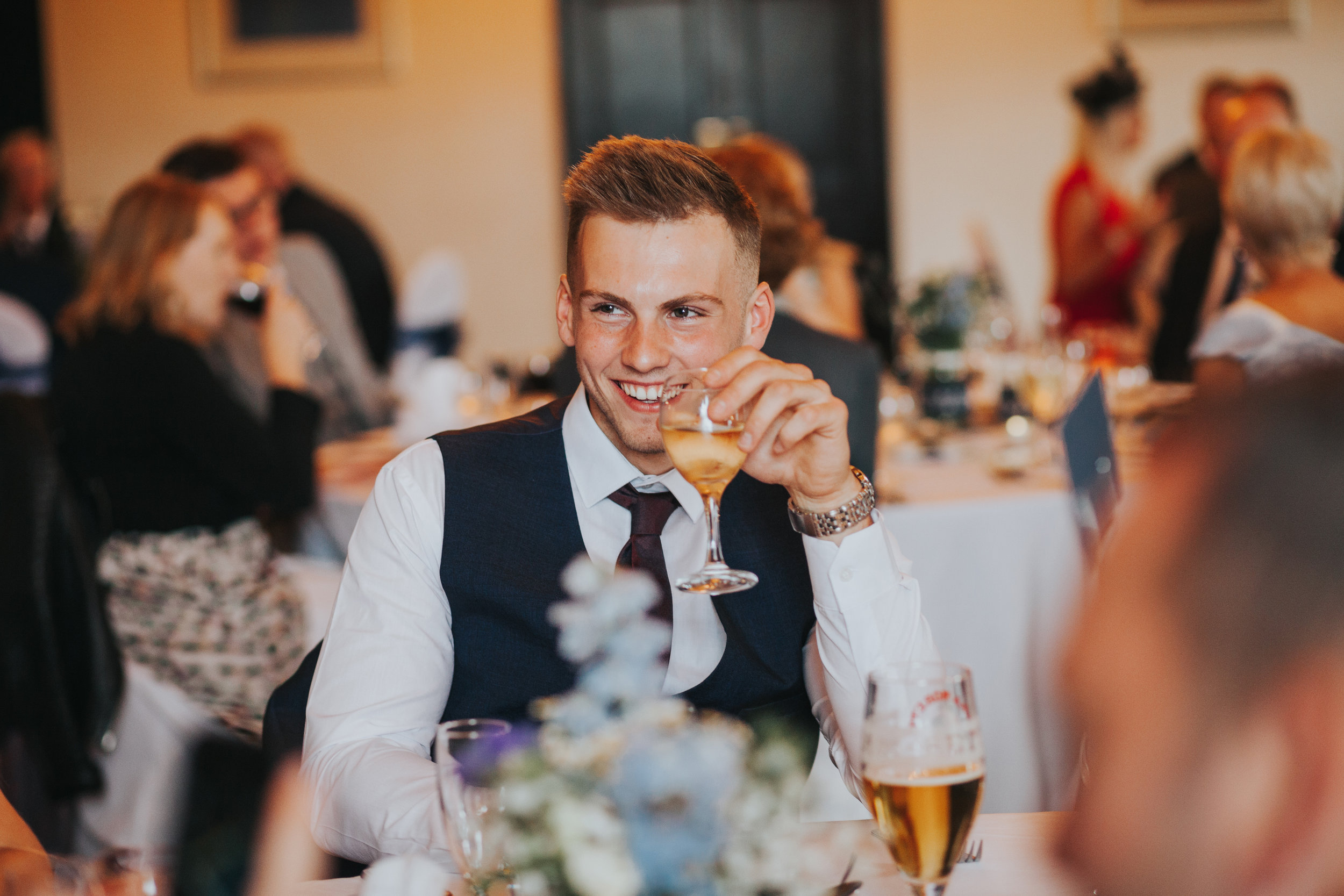 Male wedding guest enjoys some champagne while smiling.