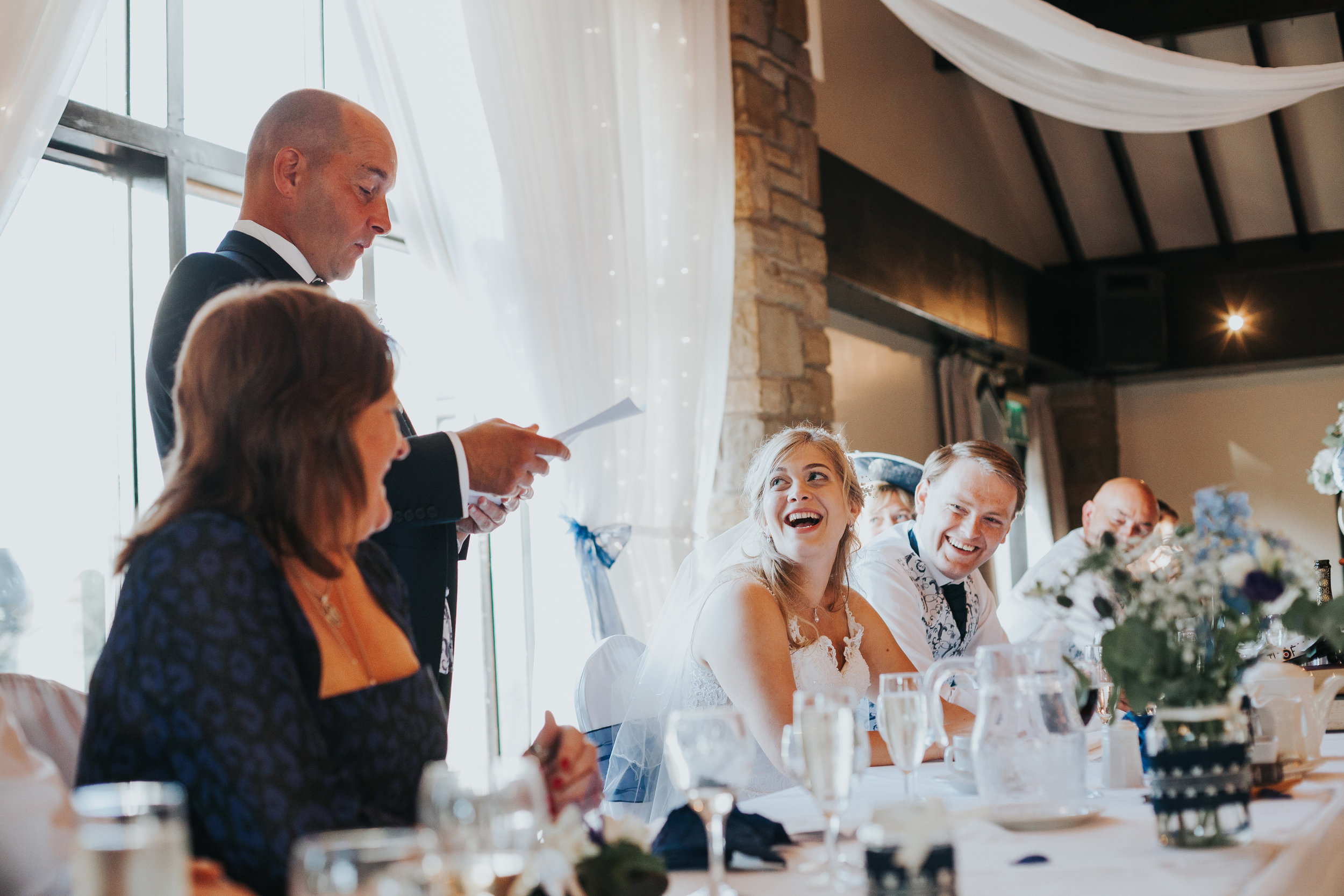 Bride laughs as her father gives a speech.