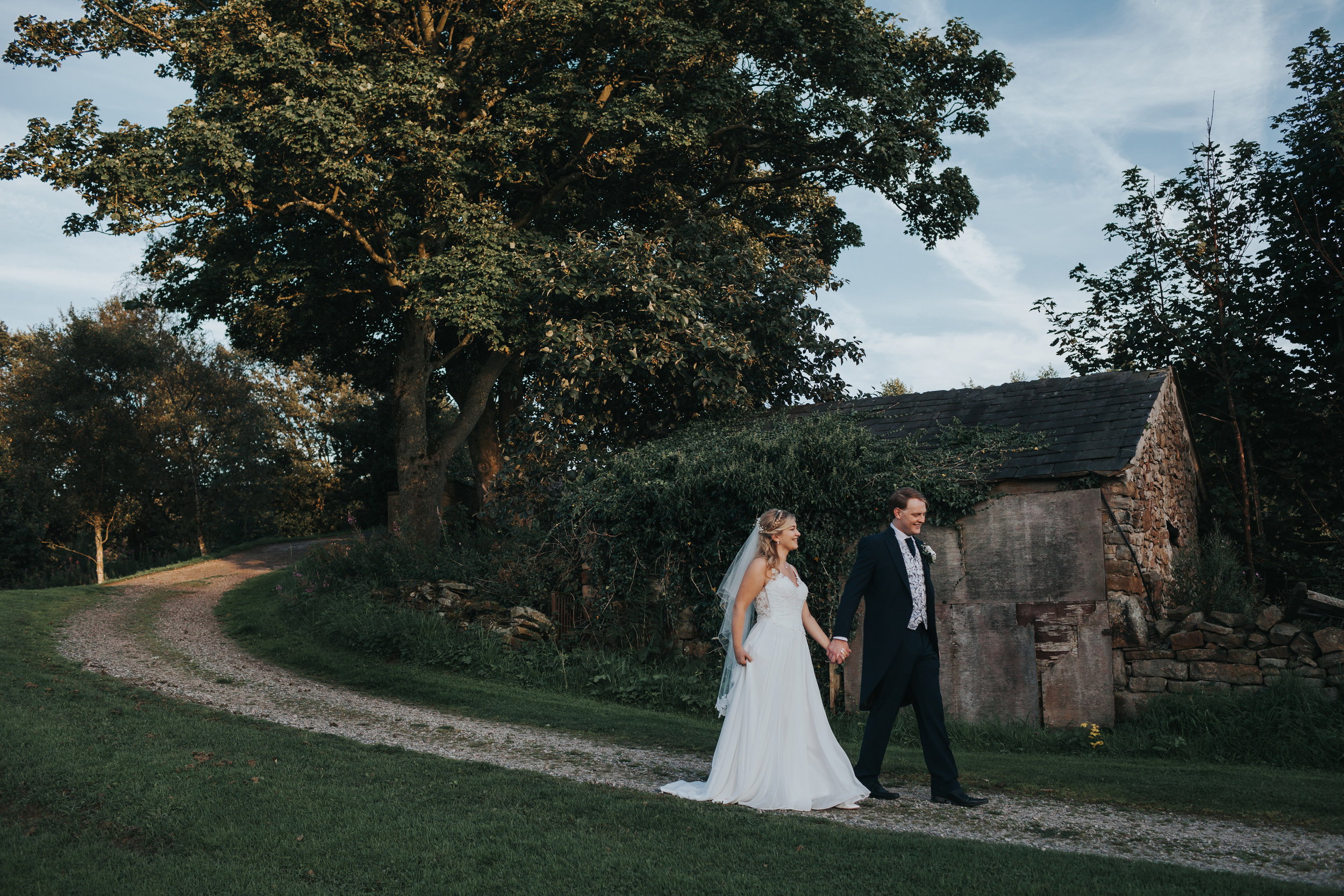 Bride and Groom walk past a derelict house.