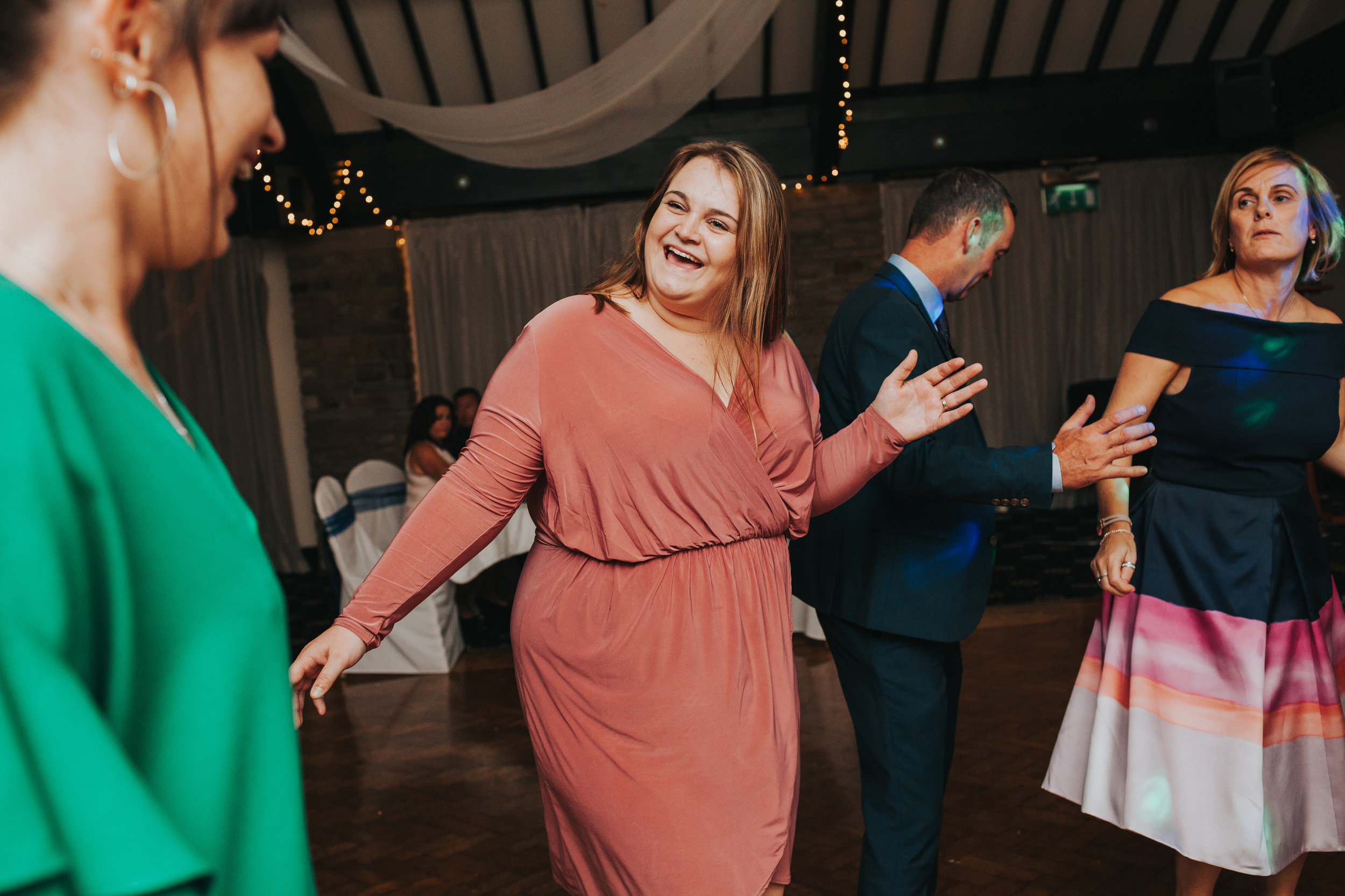 Wedding guest smiles while dancing.