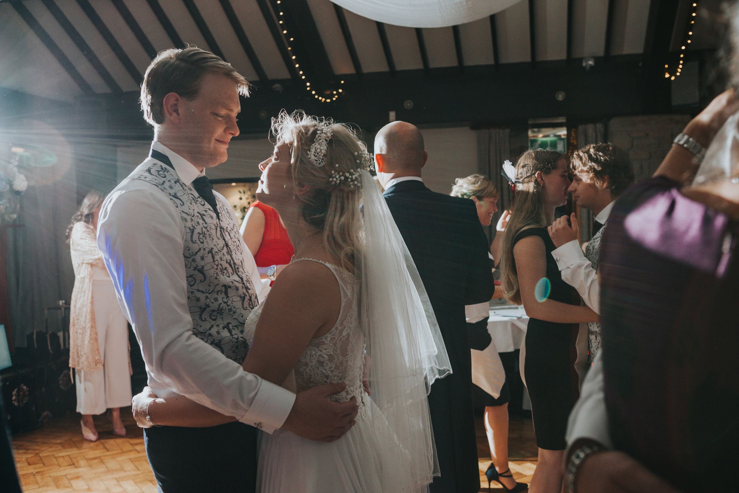 Bride and Groom look into each others eyes while dancing together.