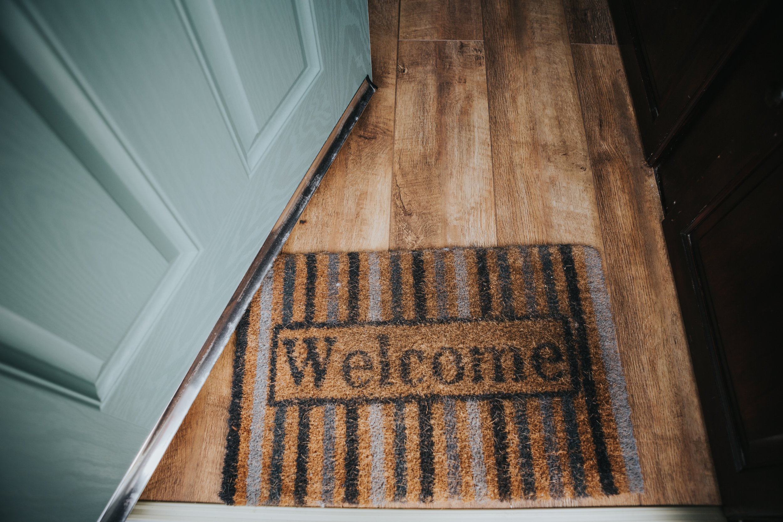"A egg shell blue door opens onto a mat that says ""Welcome"" at a families house in Liverpool."