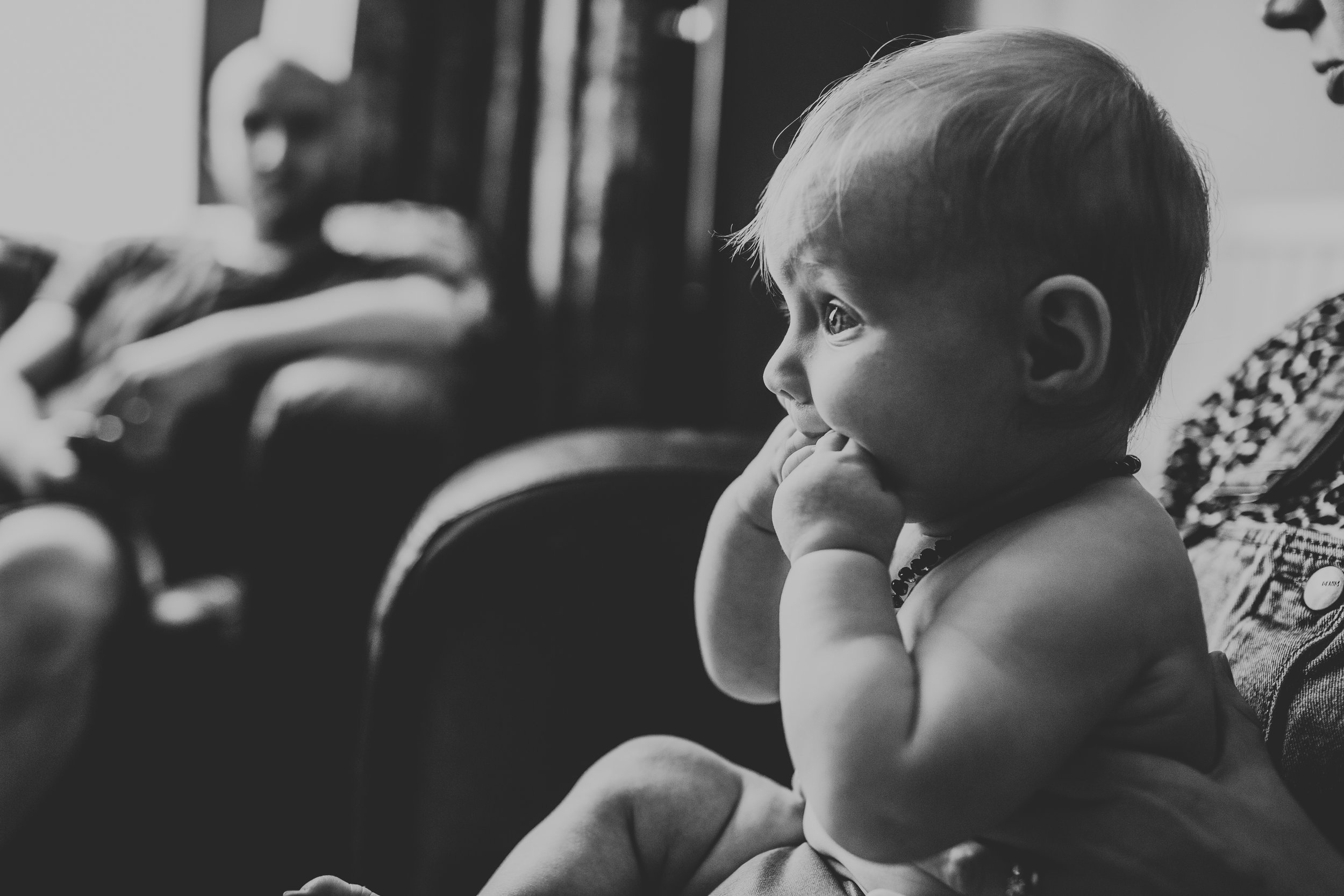 Baby watching formula one in black and white.