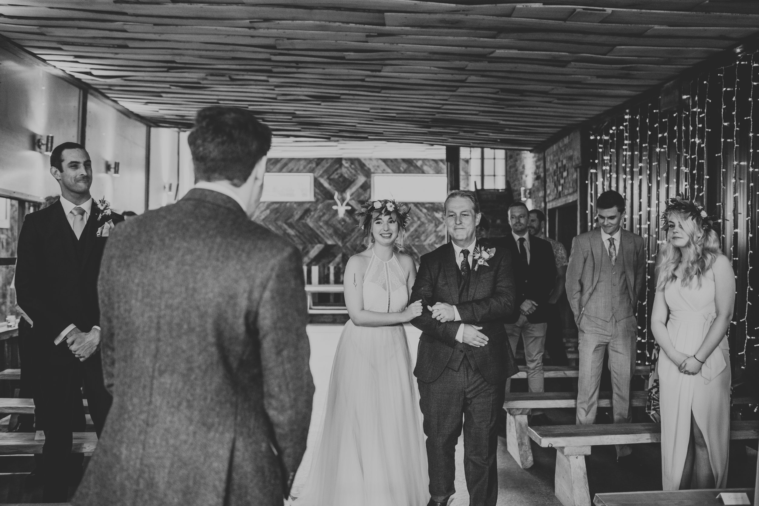Bride is walked down the aisle by father. Photograph in black and white.