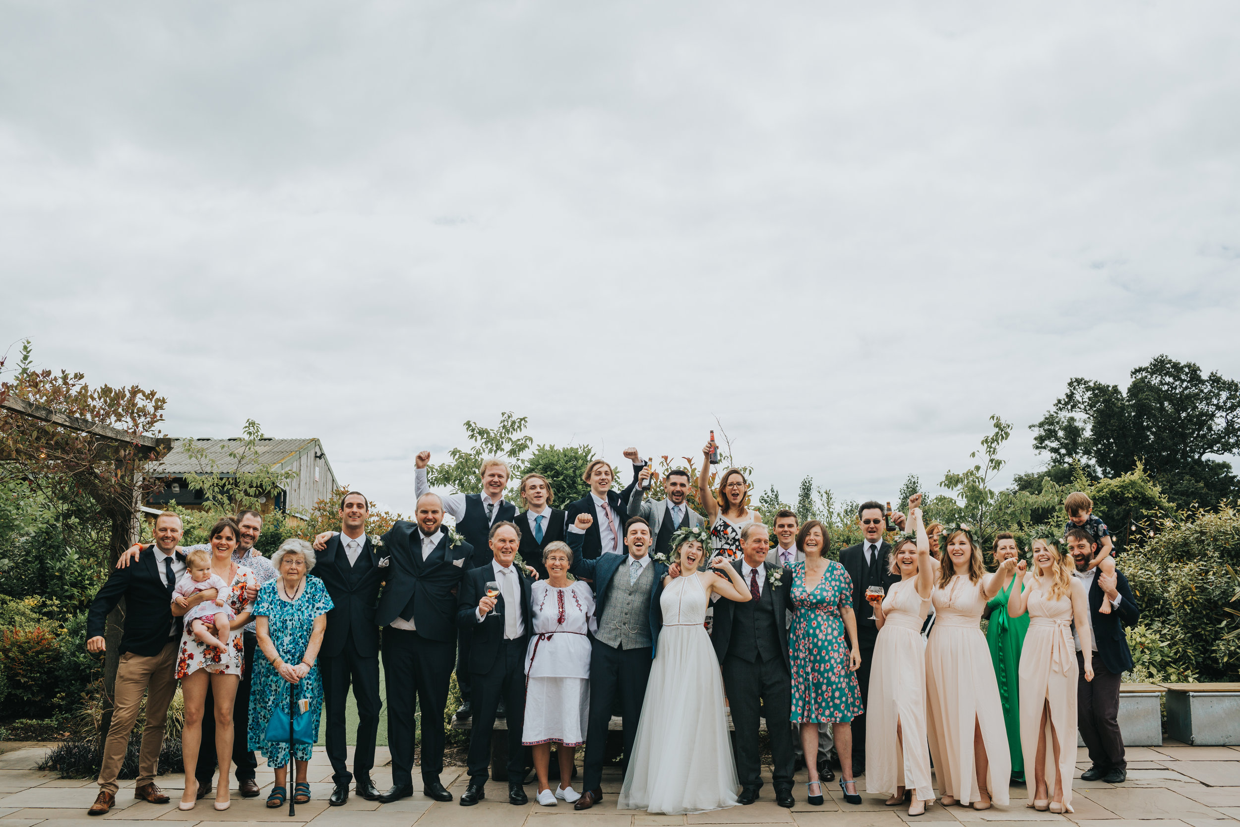 Group photograph of all the wedding guests cheering at Owen House Wedding Barn.