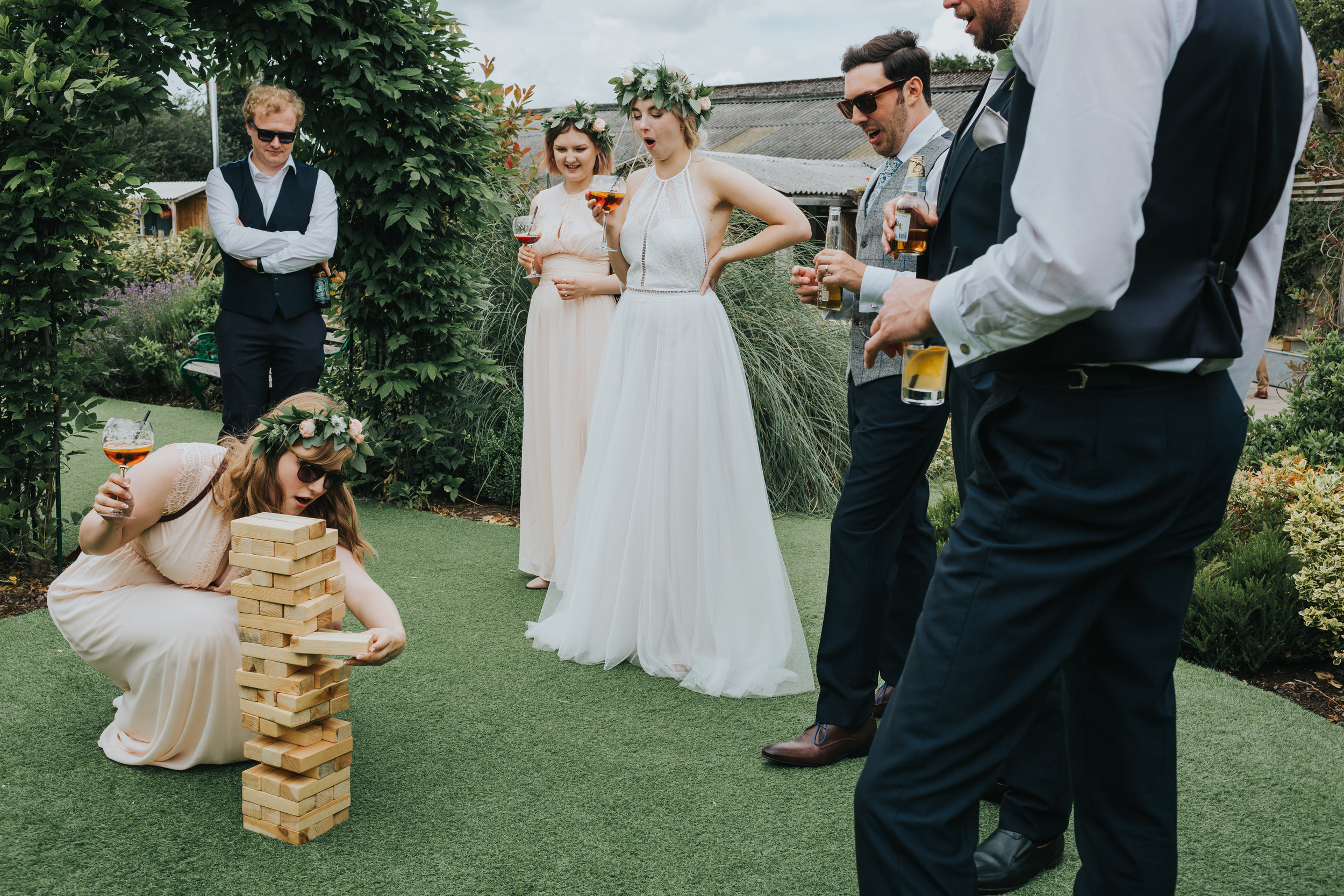 Bride, groom and bridal party watch on as bridesmaid pulls a rouge Jenga move!