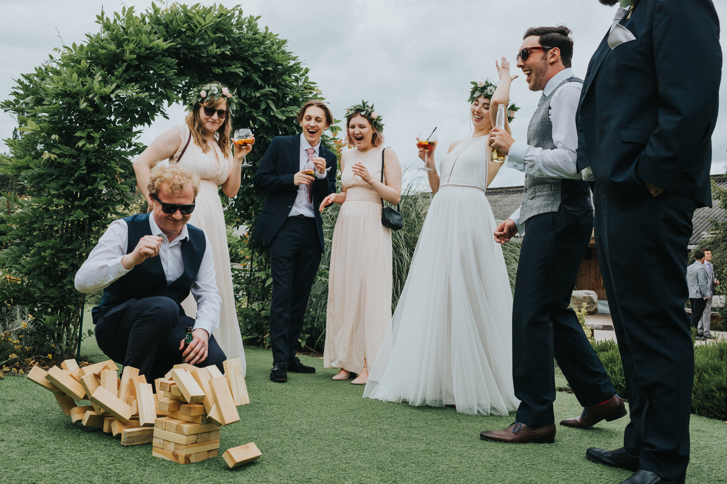 Bridal party roar with laughter as wedding guests topples the Jenga tower.