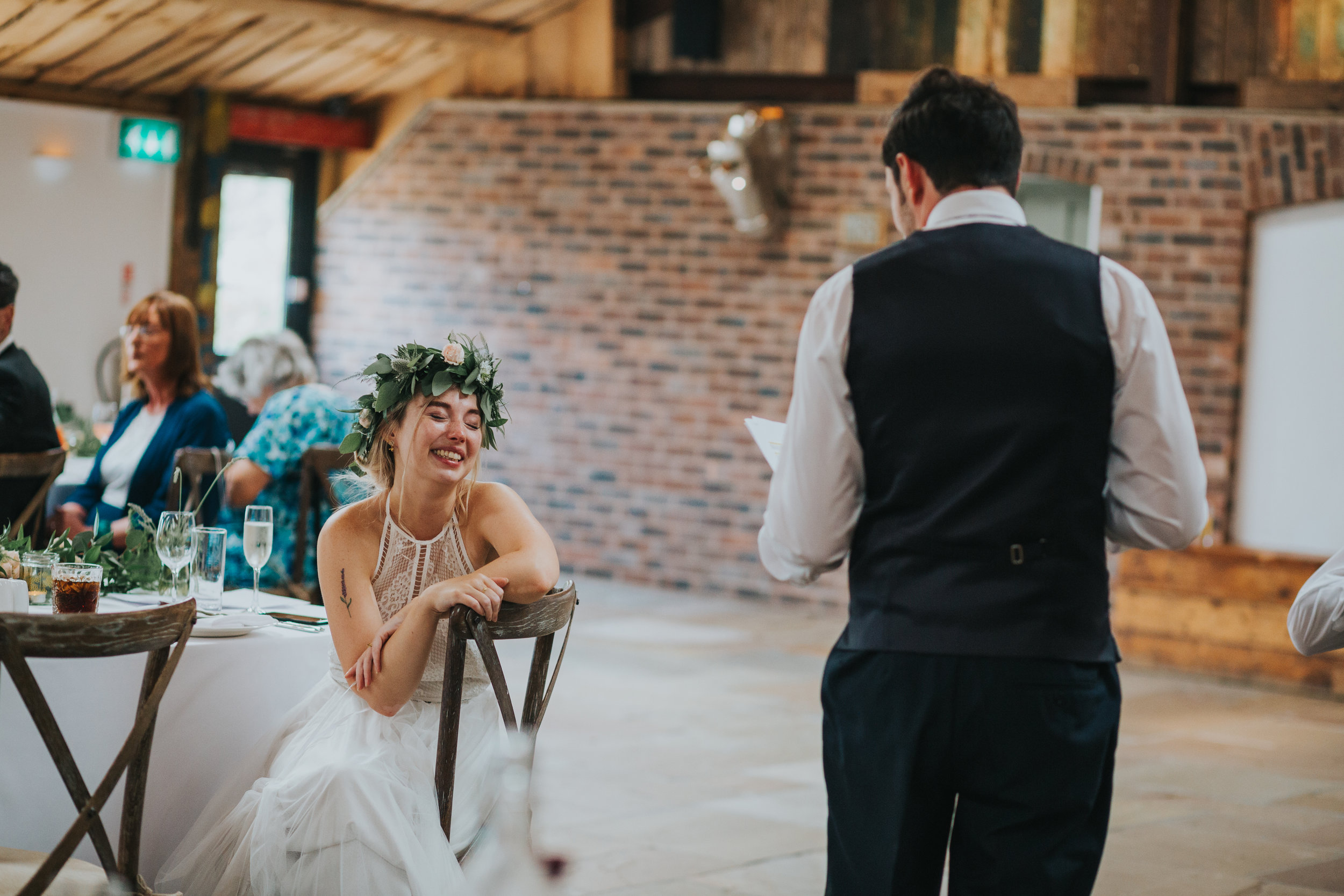 Bride laughs at her husbands speech.