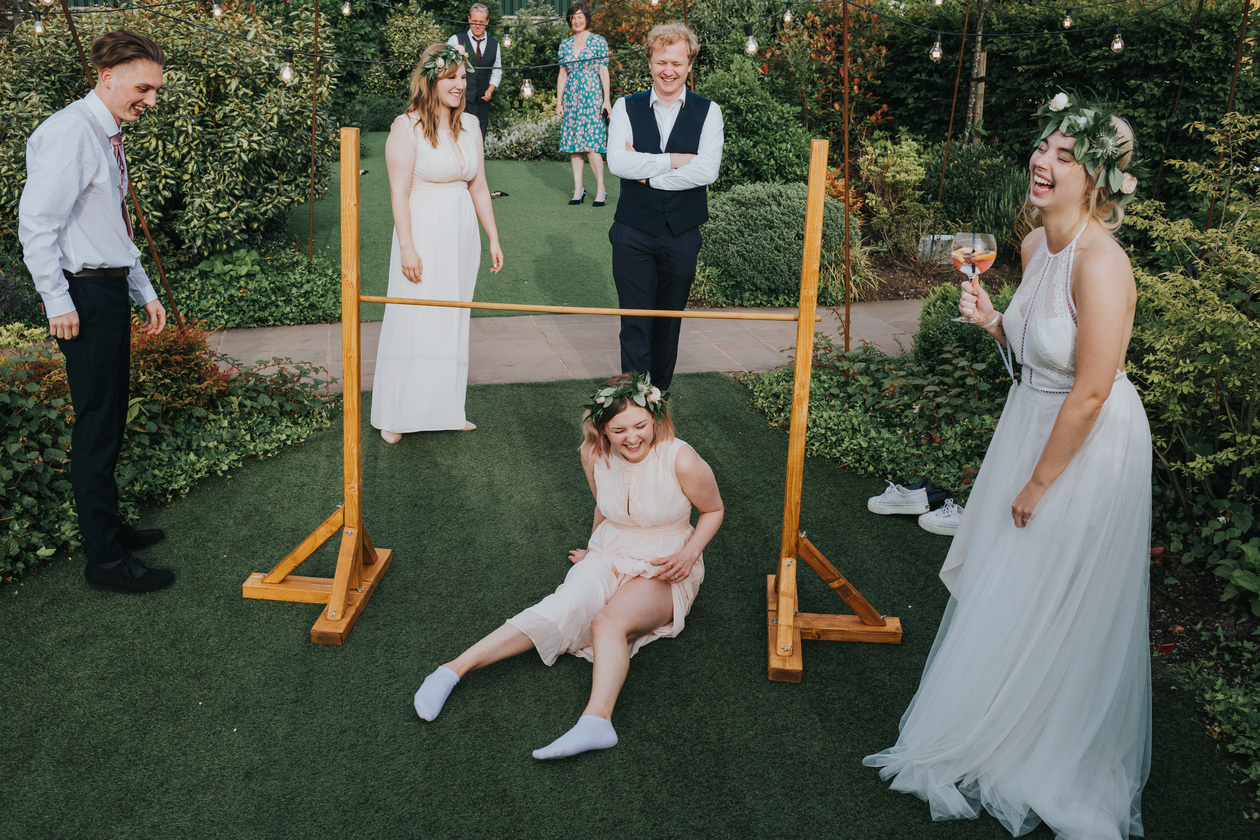 Bridesmaid falls on her bum while playing  limbo. Bride is holding her drink and laughing.