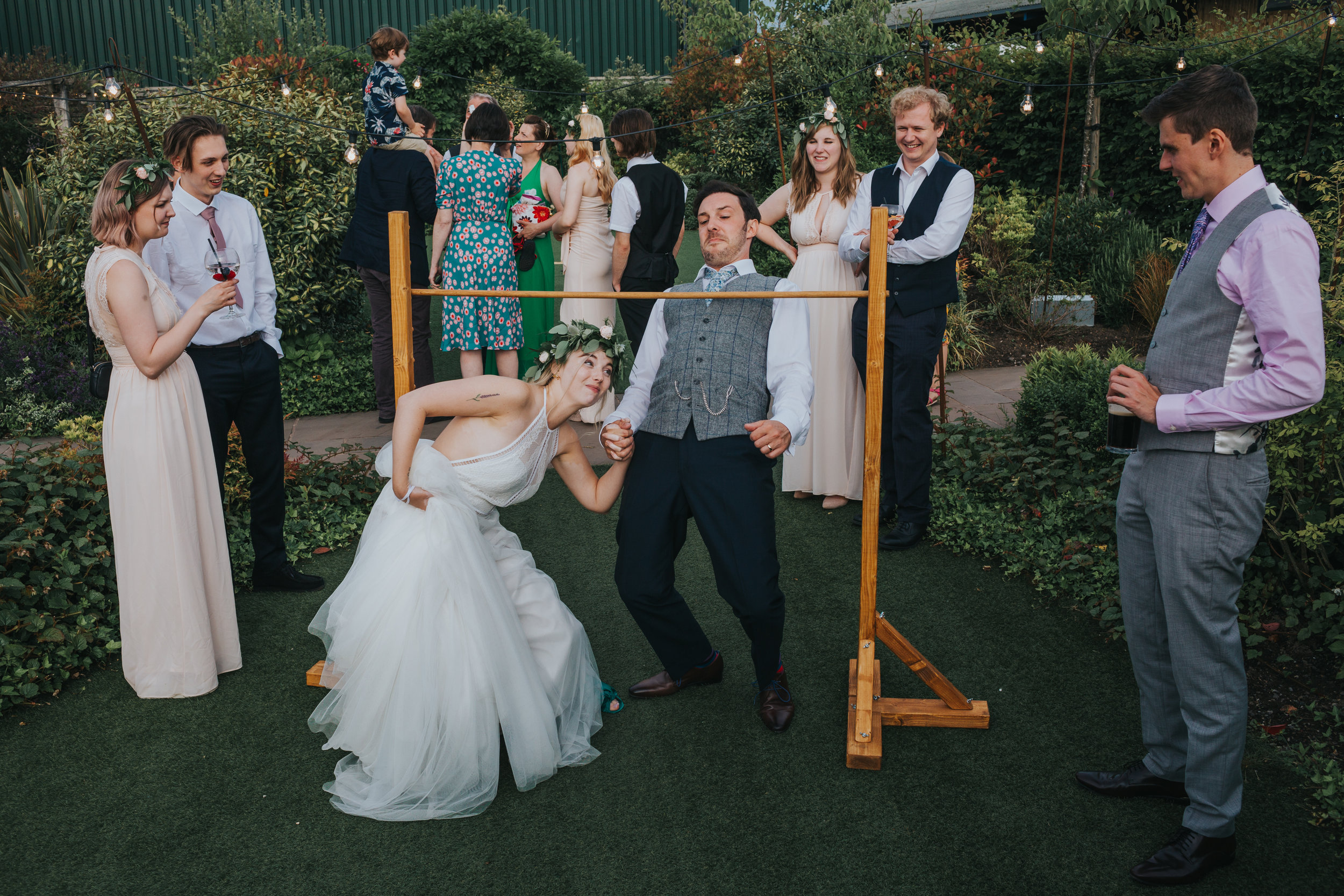 Bride and groom try and limbo together. It doesn't really work.