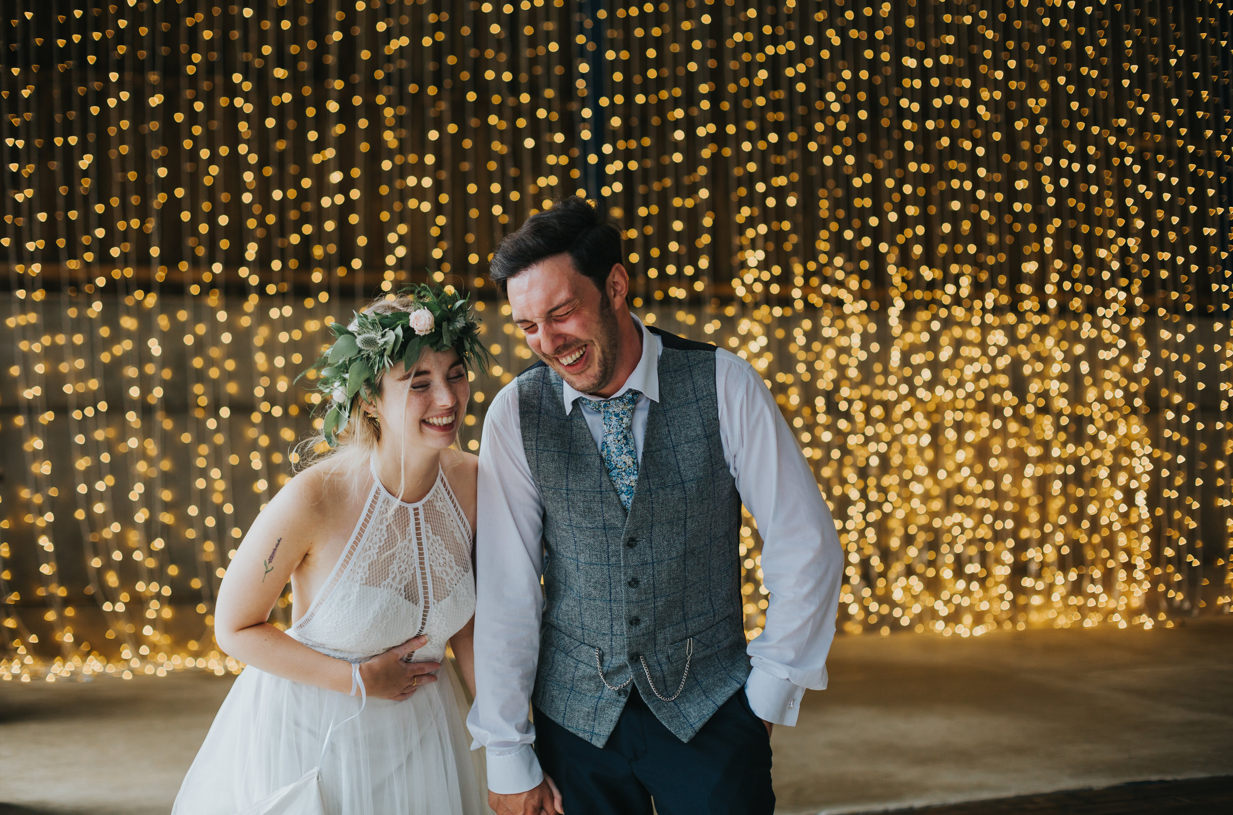 Bride and groom laugh in font of fairy lights in Owen House Wedding Barns Shooting Barn.