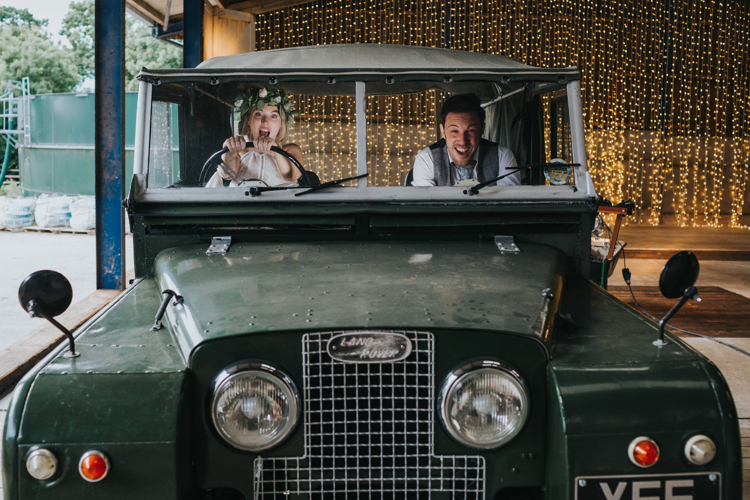 The bride and groom take the land rover for a spin. The bride is driving, but doesn't have a license. Everyone looks scared.
