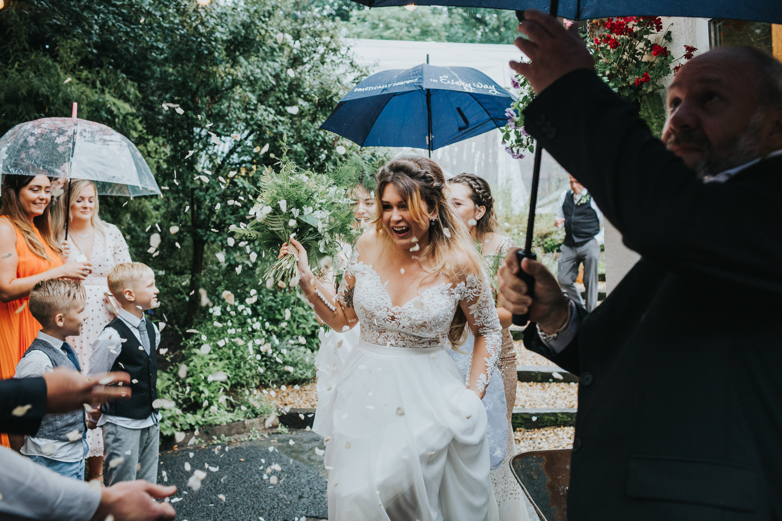 Bride makes her way out under a sea of brollies held for her by wedding guests as they throw confetti.