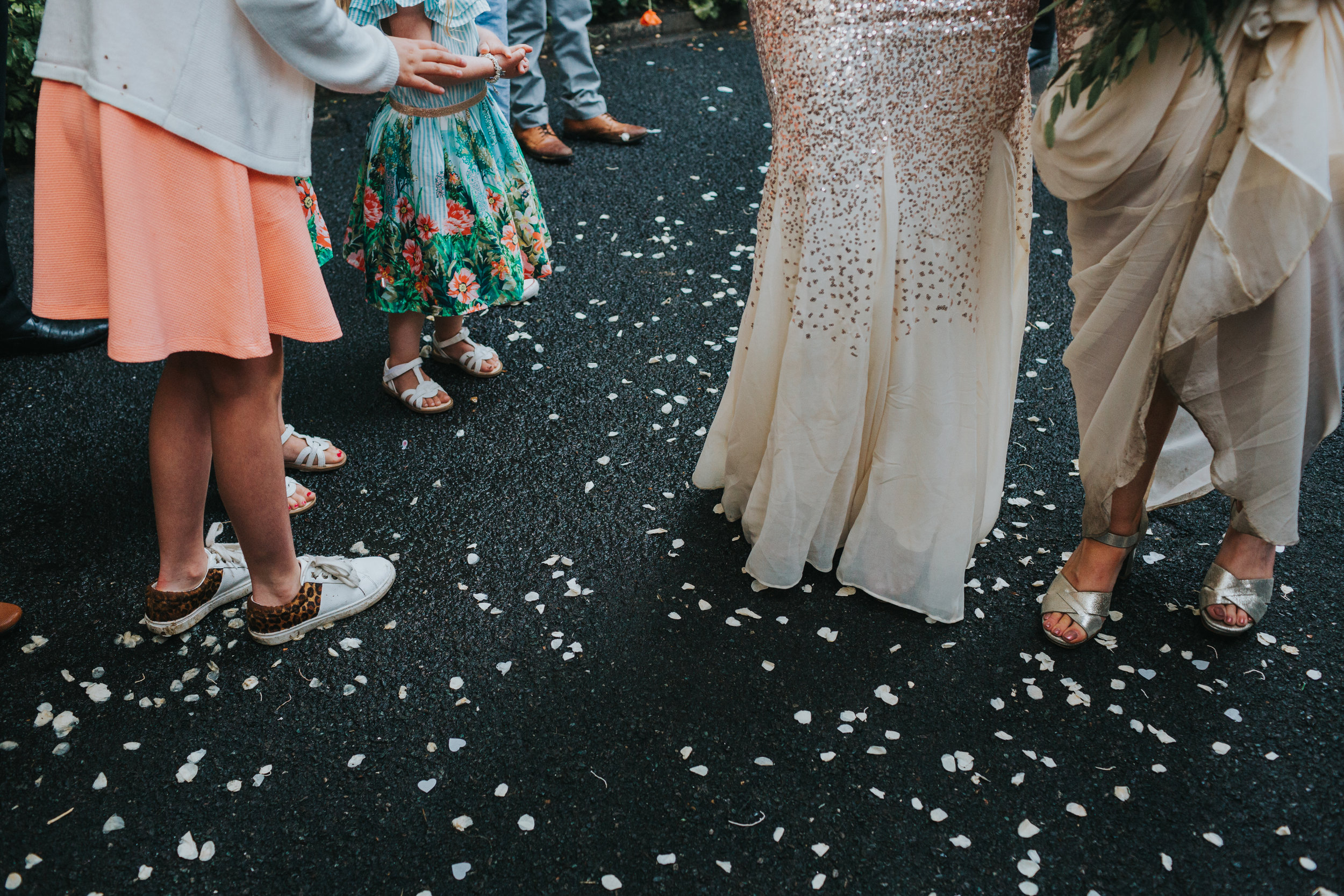 Confetti covers the floor next to wedding guests pretty shoes and dresses.