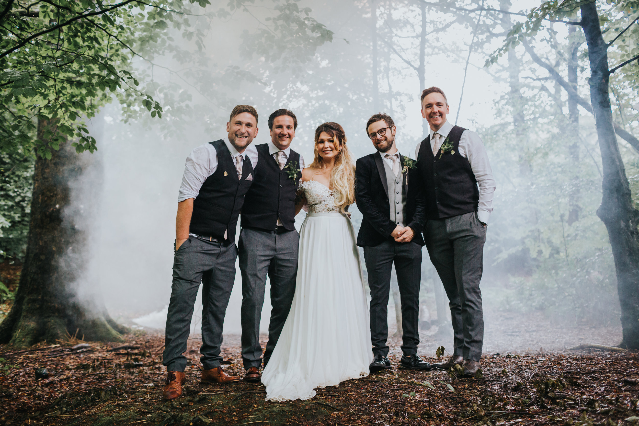 Bride and groom stand with grooms men in front of mist.