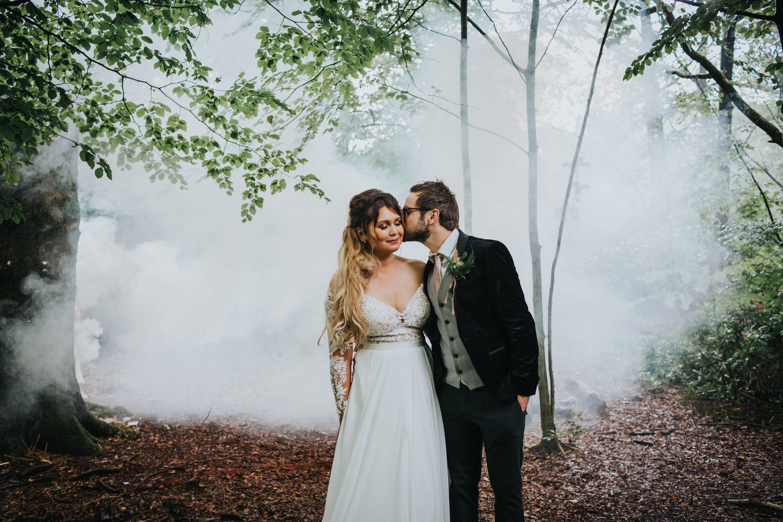 Bride and groom stand together in front of the wood land mist.