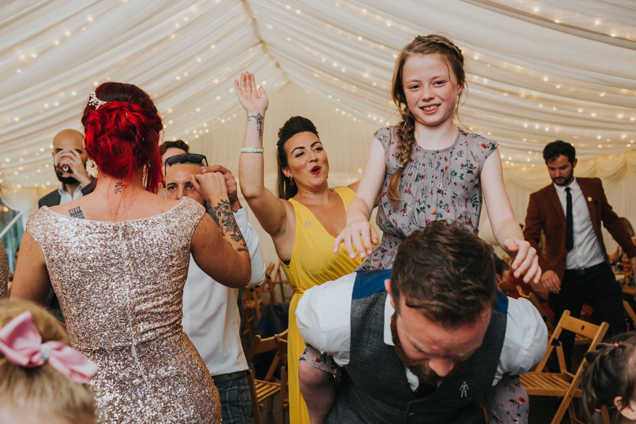 A wedding guest gives a little girl a piggy back as another wedding guest dances behind them.