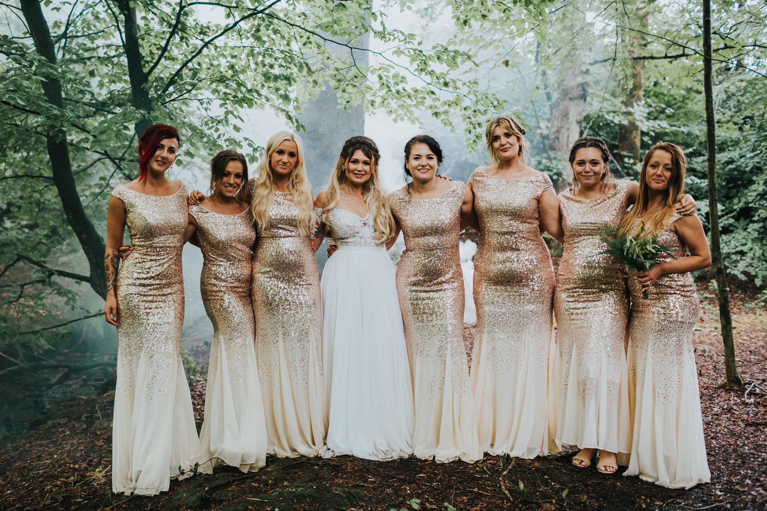 Bridesmaids stand for a photo in the woods with mist behind them.