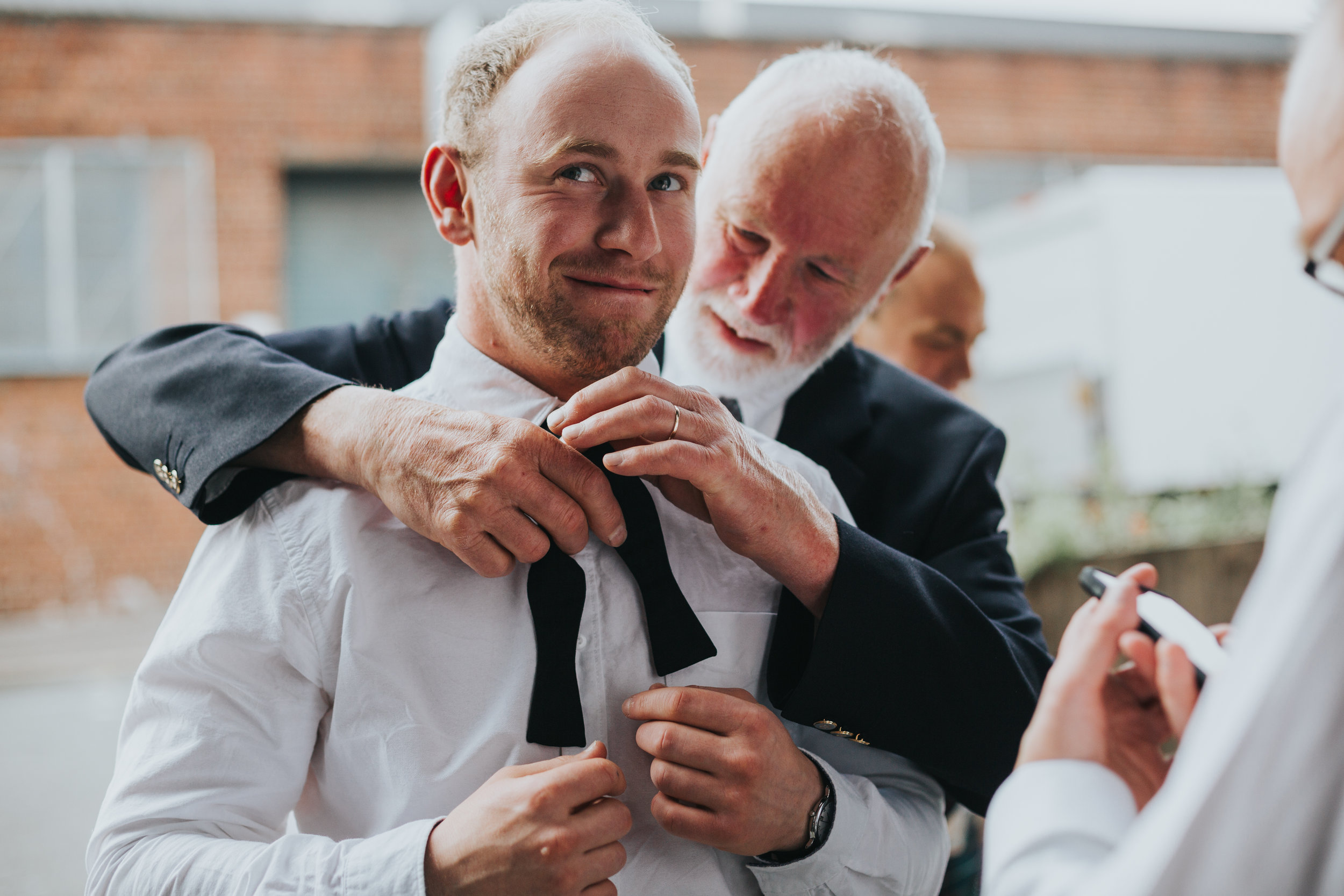 Male wedding guests has his tie fixed by another male wedding guest.